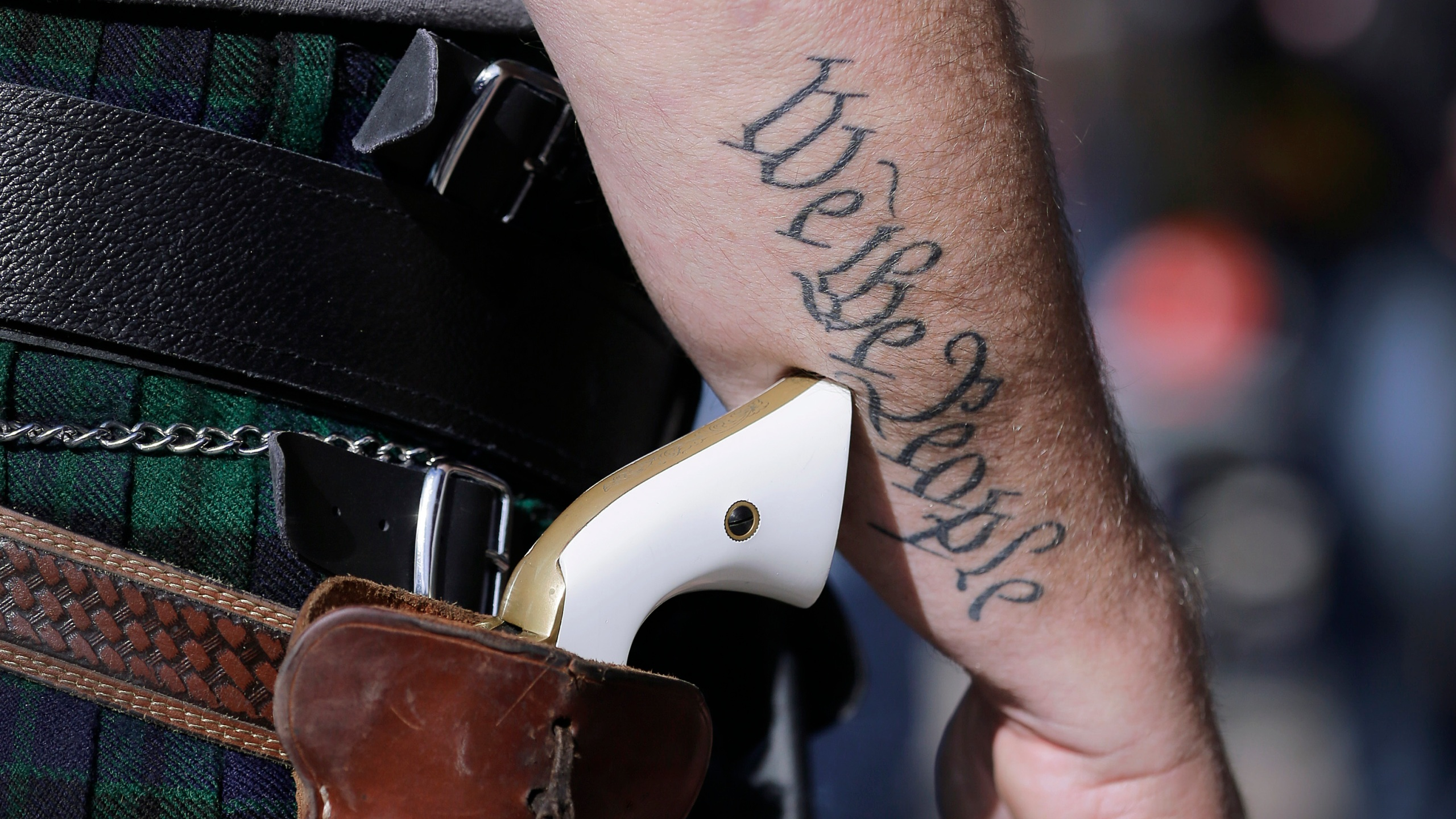 In this Jan. 26, 2015 file photo, a supporter of open carry gun laws, wears a pistol as he prepares for a rally in support of open carry gun laws at the Capitol, in Austin, Texas. Texas lawmakers have given final approval to allowing people carry handguns without a license, and the background check and training that go with it. The Republican-dominated Legislature approved the measure Monday, May 24, 2021 sending it to Gov. Abbott. (AP Photo/Eric Gay, File)