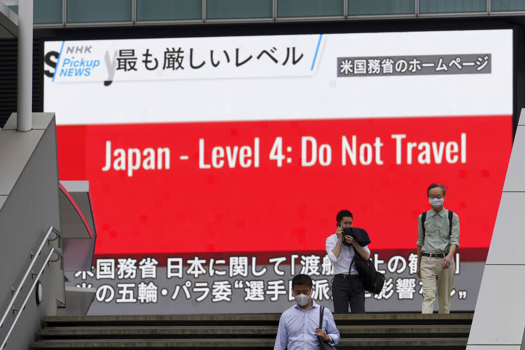 People wearing masks to help protect against the spread of the coronavirus walk in front of a screen showing the news on U.S. warning against visits to Japan Tuesday, May 25, 2021, in Tokyo. (AP Photo/Eugene Hoshiko)