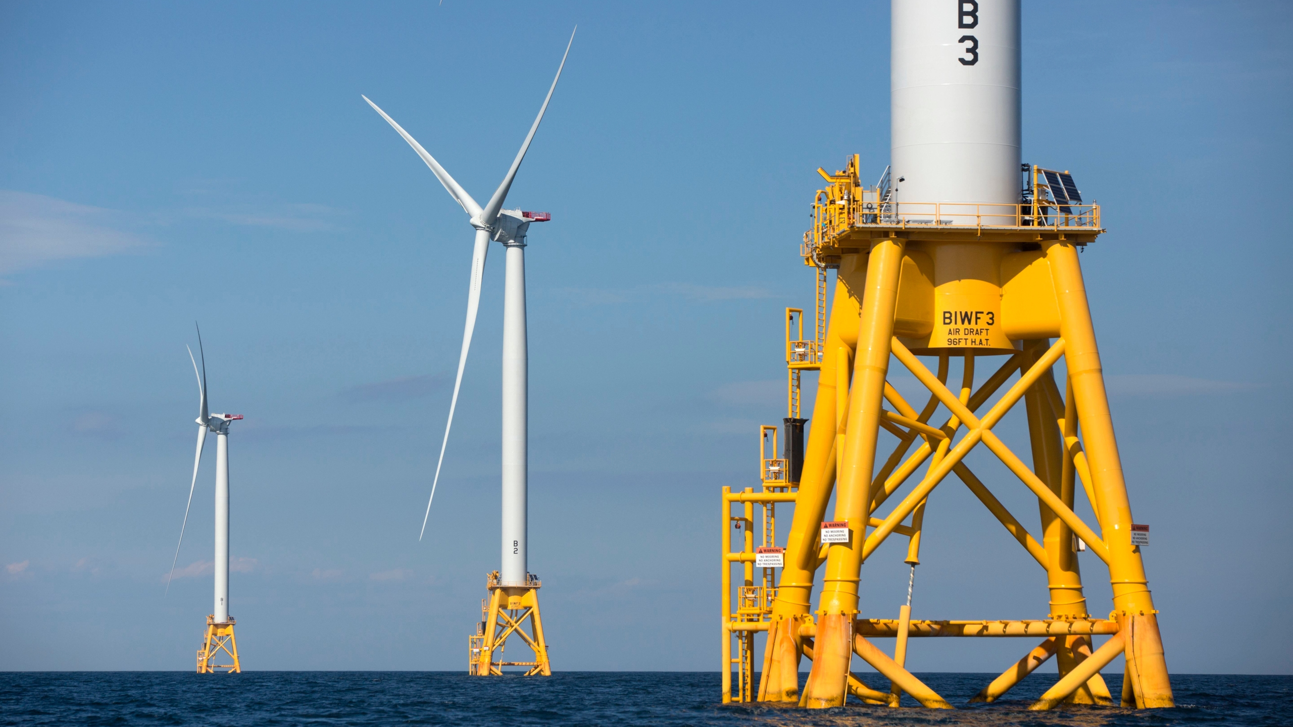 In this Aug. 15, 2016 file photo, three of Deepwater Wind's five turbines stand in the water off Block Island, R.I, the nation's first offshore wind farm. California and the federal government have agreed to open up areas off the central and northern coasts to massive wind farms. The pact announced Tuesday, May 25, 2021, that would float hundreds of turbines off the coast of Morro Bay and Humboldt Bay was touted as a breakthrough to eventually power 1.6 million homes. (AP Photo/Michael Dwyer, File)