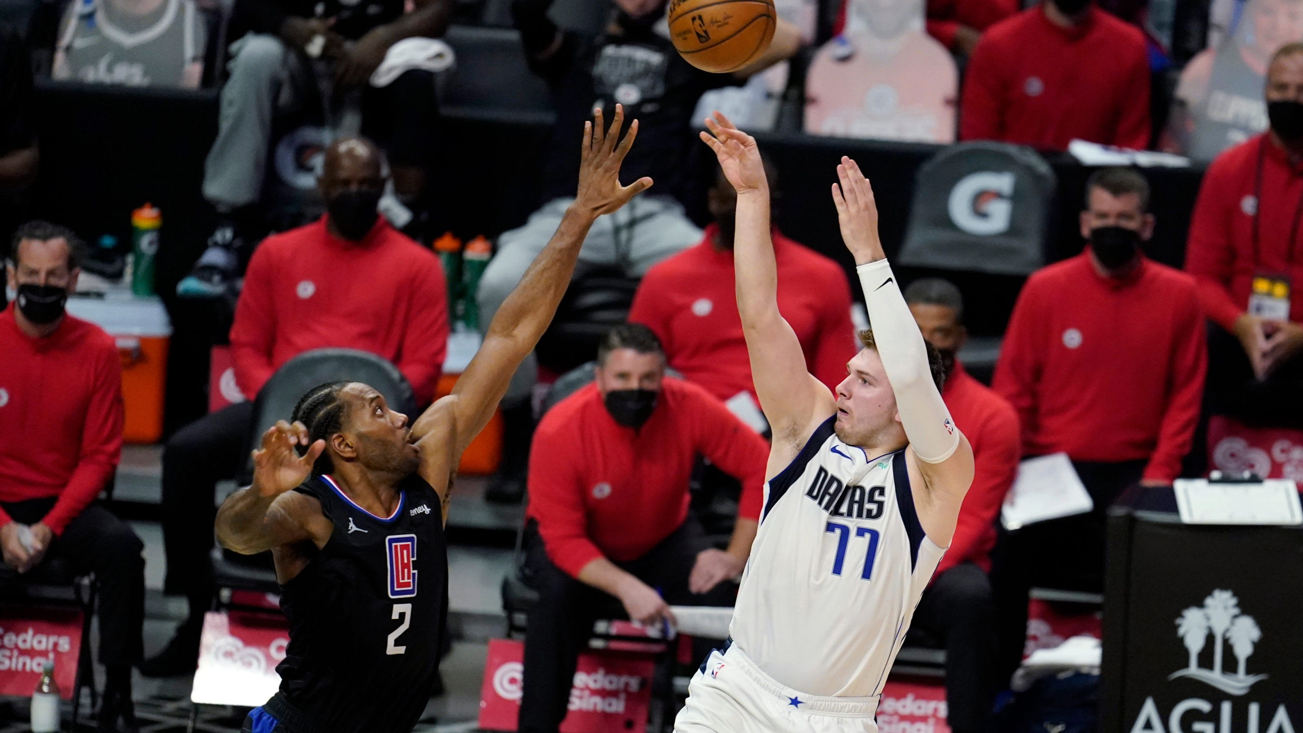 Dallas Mavericks guard Luka Doncic (77) scores over Los Angeles Clippers forward Kawhi Leonard (2) during the second half in Game 2 of an NBA basketball first-round playoff series on May 25, 2021, in Los Angeles. (AP Photo/Marcio Jose Sanchez)