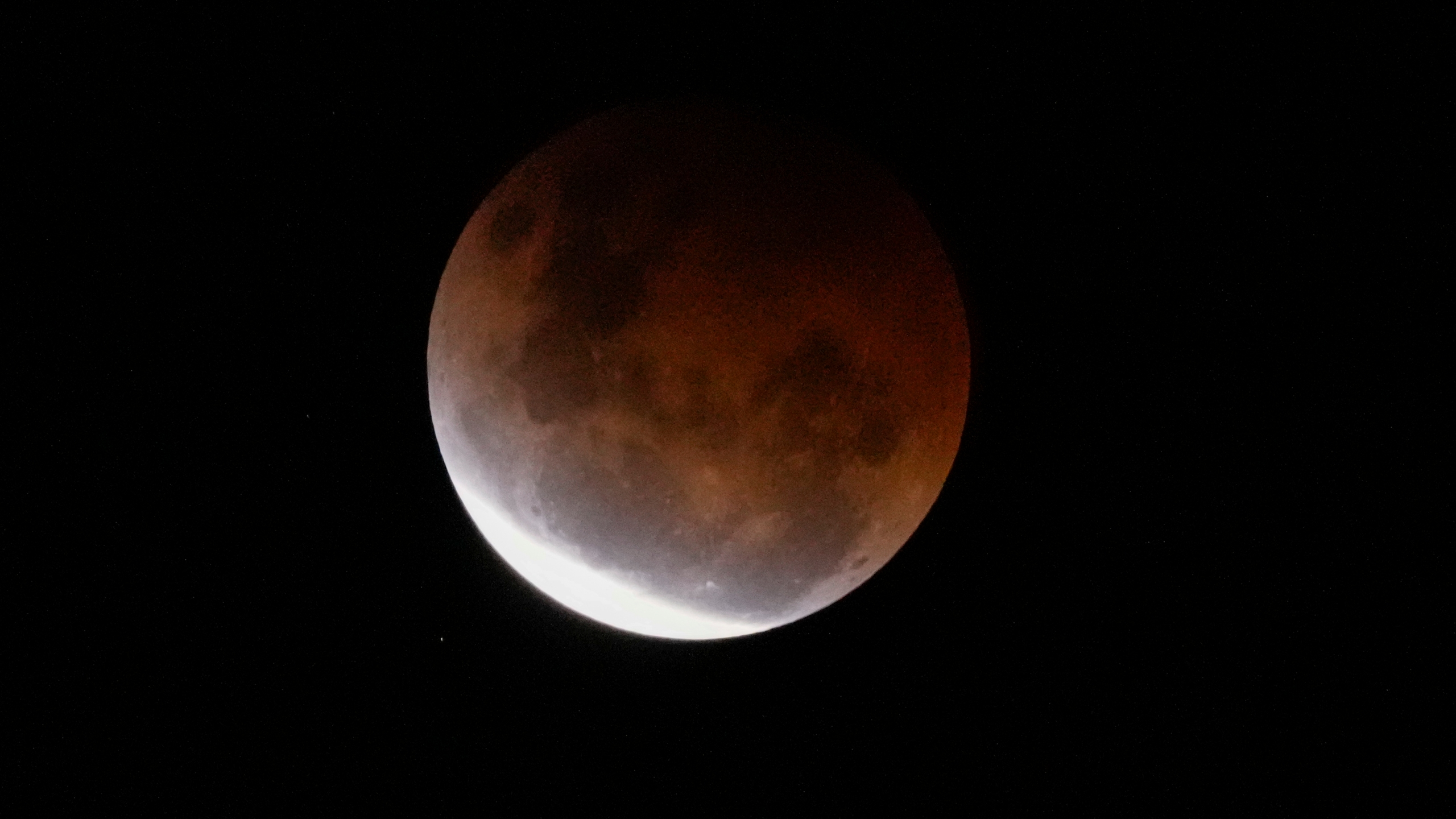 The Earth's shadow falls across the full moon above Sydney, Australia, Wednesday, May 26, 2021. The total lunar eclipse, also known as a super blood moon is the first in two years with the reddish-orange color the result of all the sunrises and sunsets in Earth's atmosphere projected onto the surface of the eclipsed moon. (AP Photo/Mark Baker)
