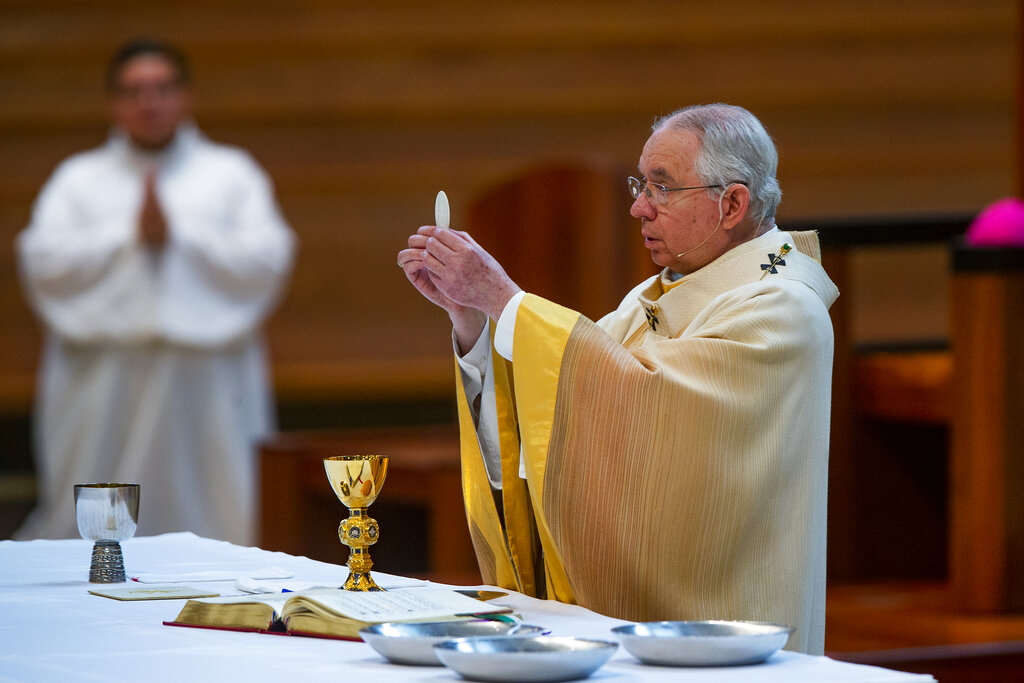 In this Sunday, June 7, 2020 file photo, Archbishop Jose H. Gomez holds a Communion wafer as he celebrates the the Solemnity of the Most Holy Trinity, a Mass with churchgoers present at the Cathedral of Our Lady of the Angels in downtown Los Angeles. (AP Photo/Damian Dovarganes, File)
