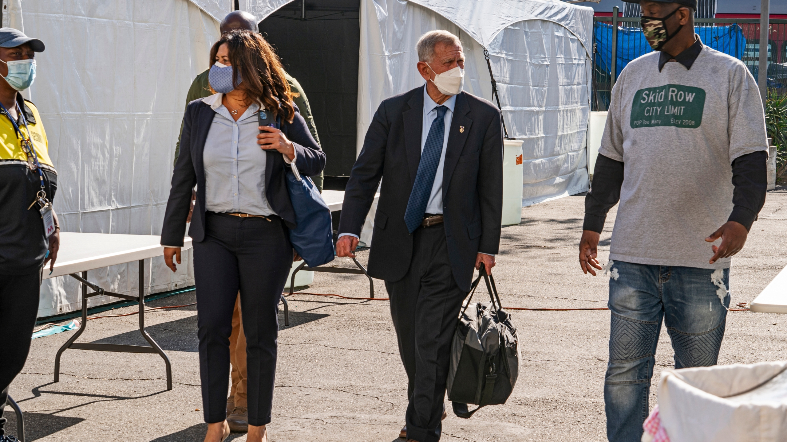 In this Feb. 4, 2021, file photo, Jeff Page, a homelessness activist, walks with U.S. District Court Judge David O. Carter, middle, and Michele Martinez, special master on the issues of homelessness, after a court hearing at Downtown Women's Center in Los Angeles. (AP Photo/Damian Dovarganes, File)