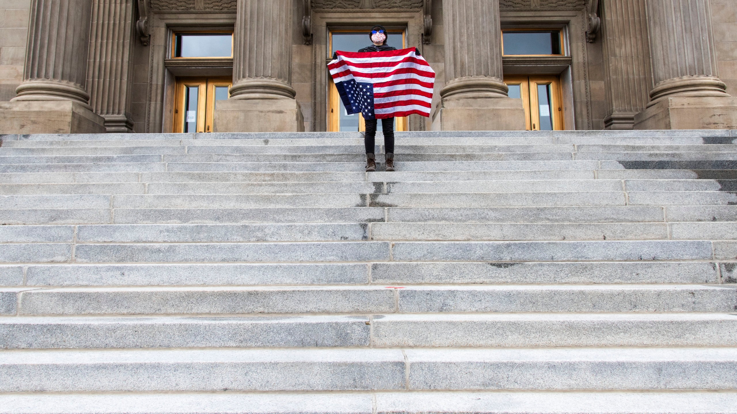"""In this April 26, 2021, file photo, a student holding a U.S. flag upside down stands atop the steps at the Idaho Capitol building in Boise. The Idaho Senate has approved legislation aimed at preventing schools and universities from """"indoctrinating"""" students through teaching critical race theory, which examines the ways in which race and racism influence American politics, culture and the law. (Darin Oswald/Idaho Statesman via AP, File)"""