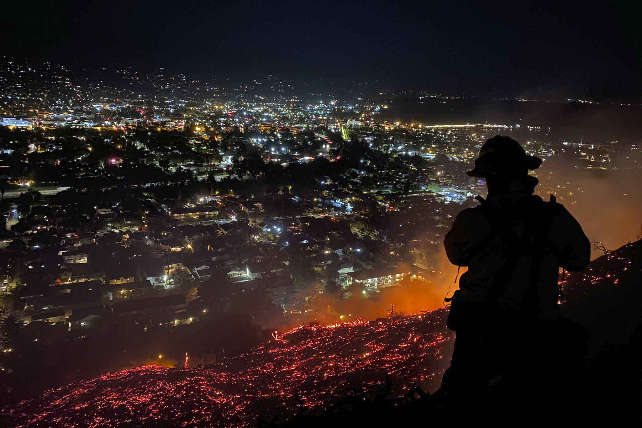 In this photo provided by the Santa Barbara County Fire Department, firefighters battle the Loma Fire in Santa Barbara on May 20, 2021.