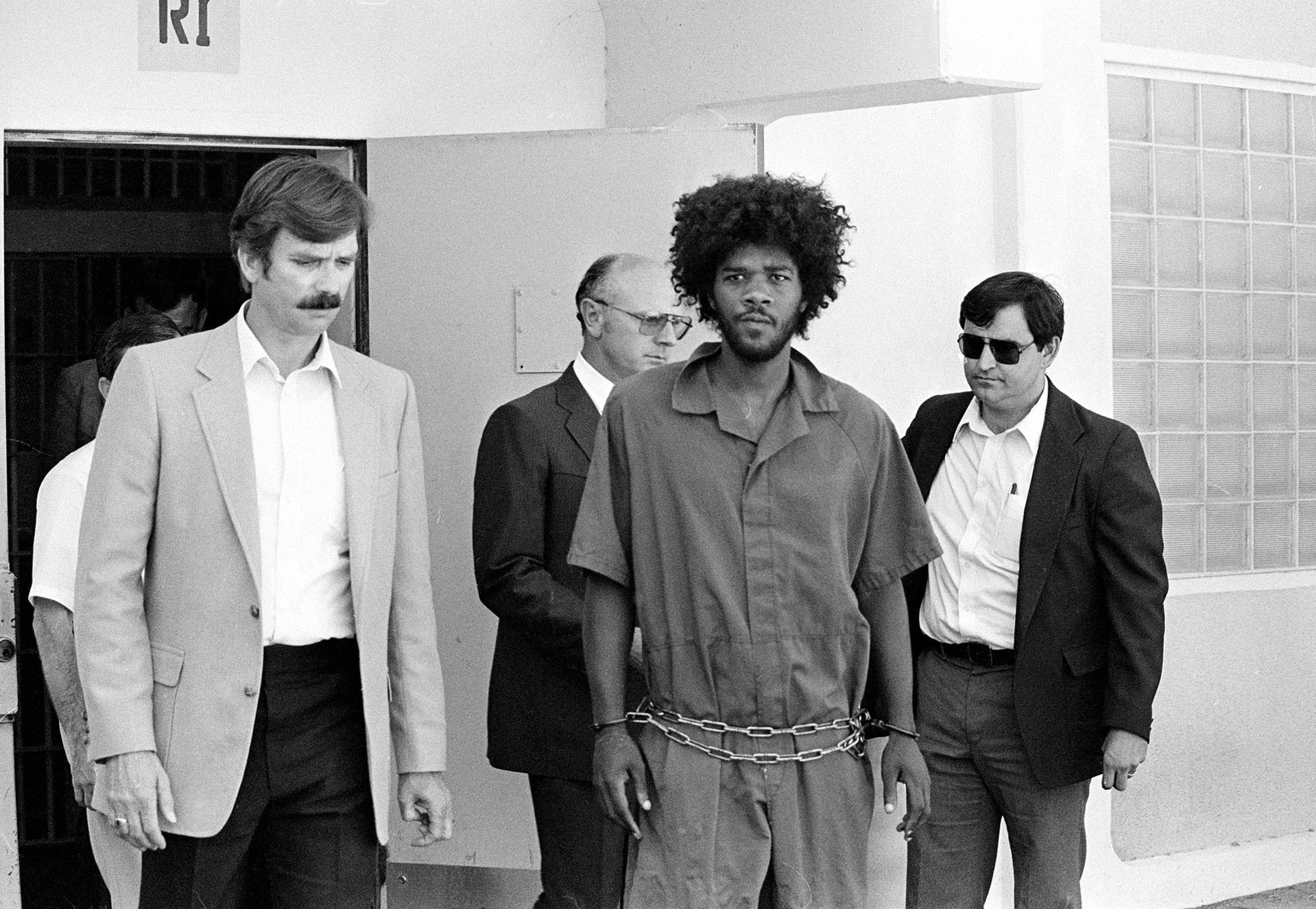 In this July 31, 1983, file photo, Kevin Cooper, center, a suspect in connection with the slashing death of four people in Chino, Calif., is escorted to a car for transport to San Bernardino from Santa Barbara, Calif., after he was arrested by police at Santa Cruz Island. (AP Photo/File)