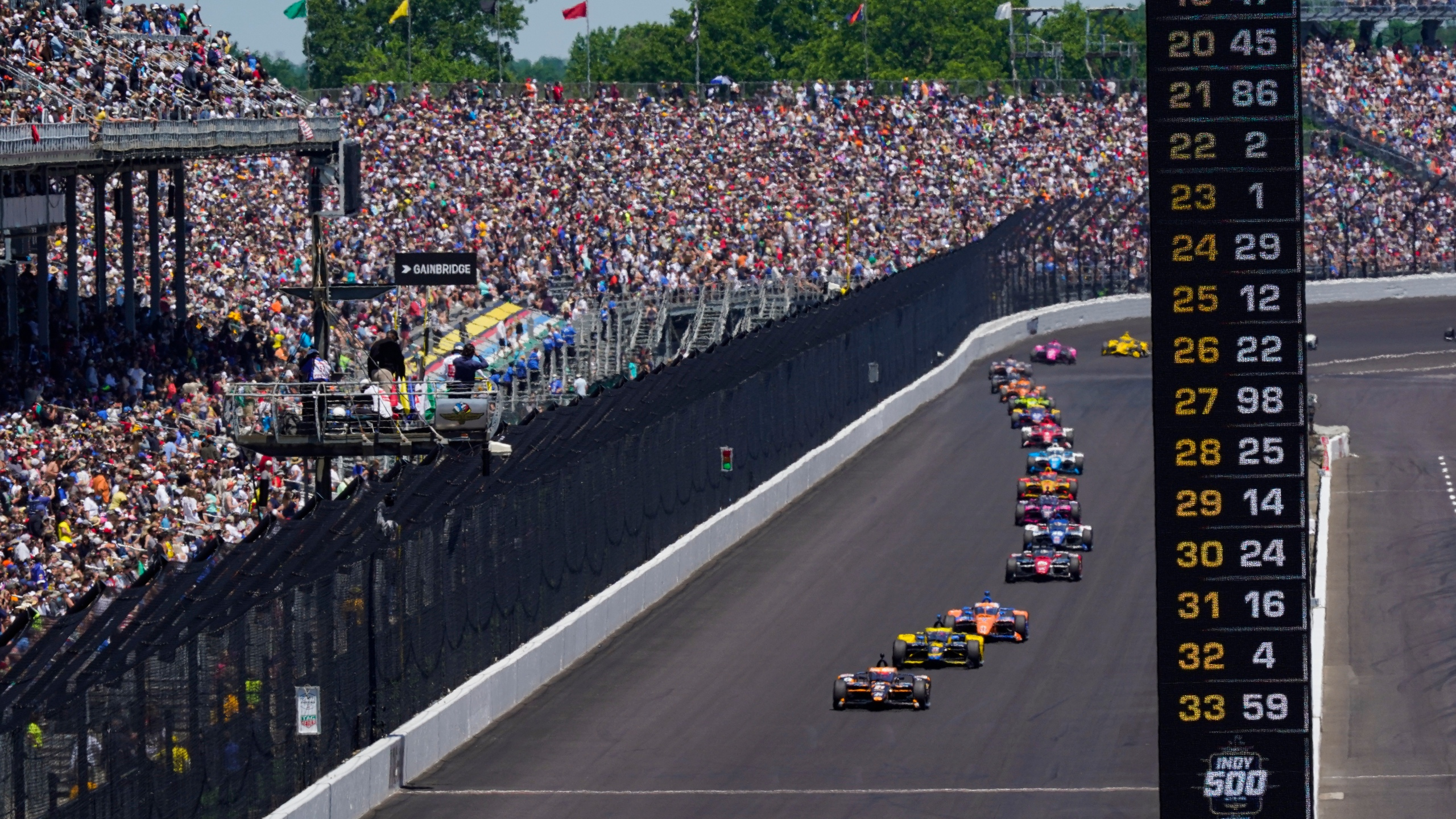 Fans fill the stands as Colton Herta leads the field in the early laps of the Indianapolis 500 auto race at Indianapolis Motor Speedway in Indianapolis, Sunday, May 30, 2021. (AP Photo/Paul Sancya)