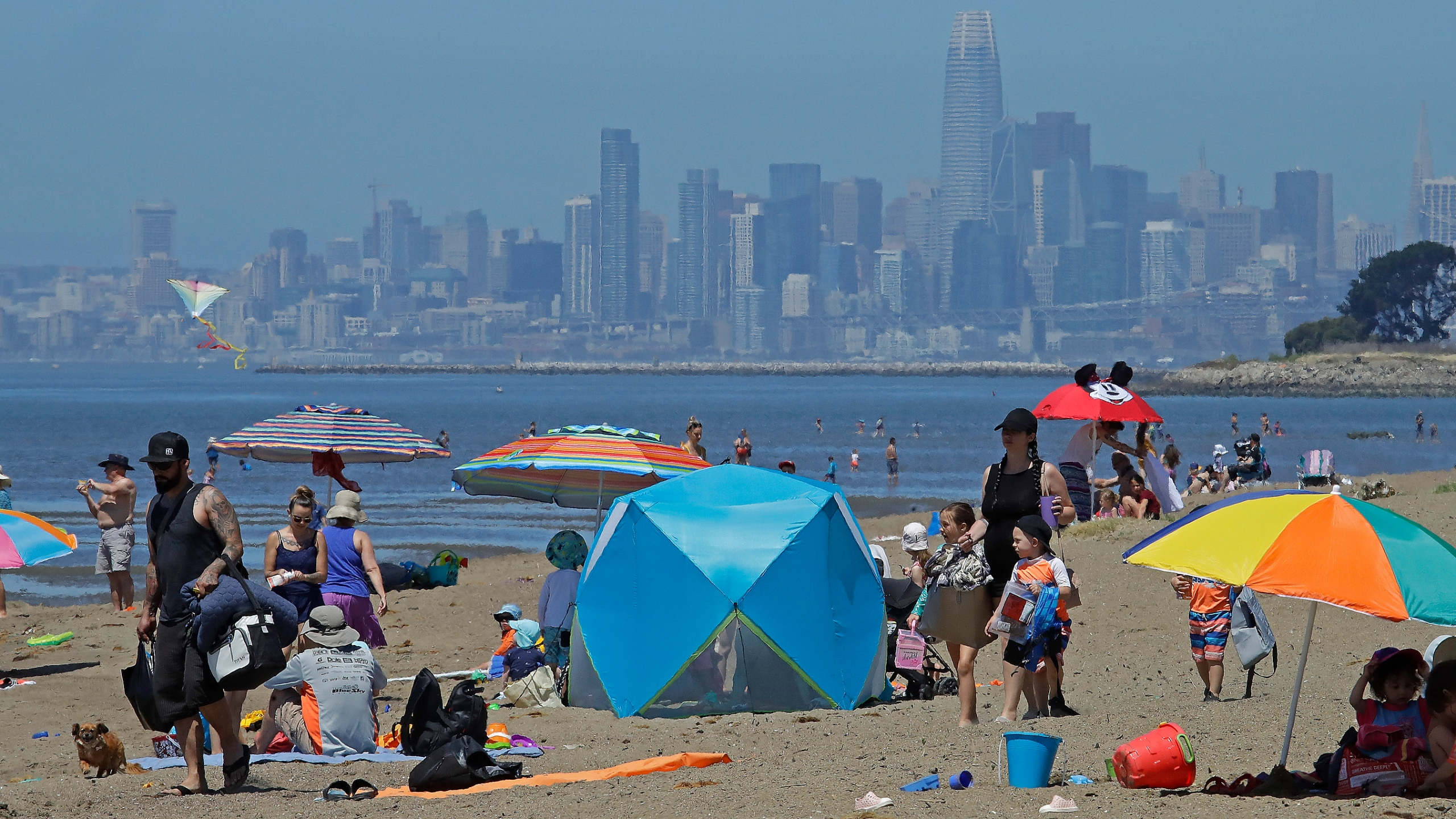In this May 26, 2020, file photo, people congregate on Robert W. Crown Memorial State Beach with the San Francisco skyline as a backdrop in Alameda, Calif. (AP Photo/Ben Margot, File)