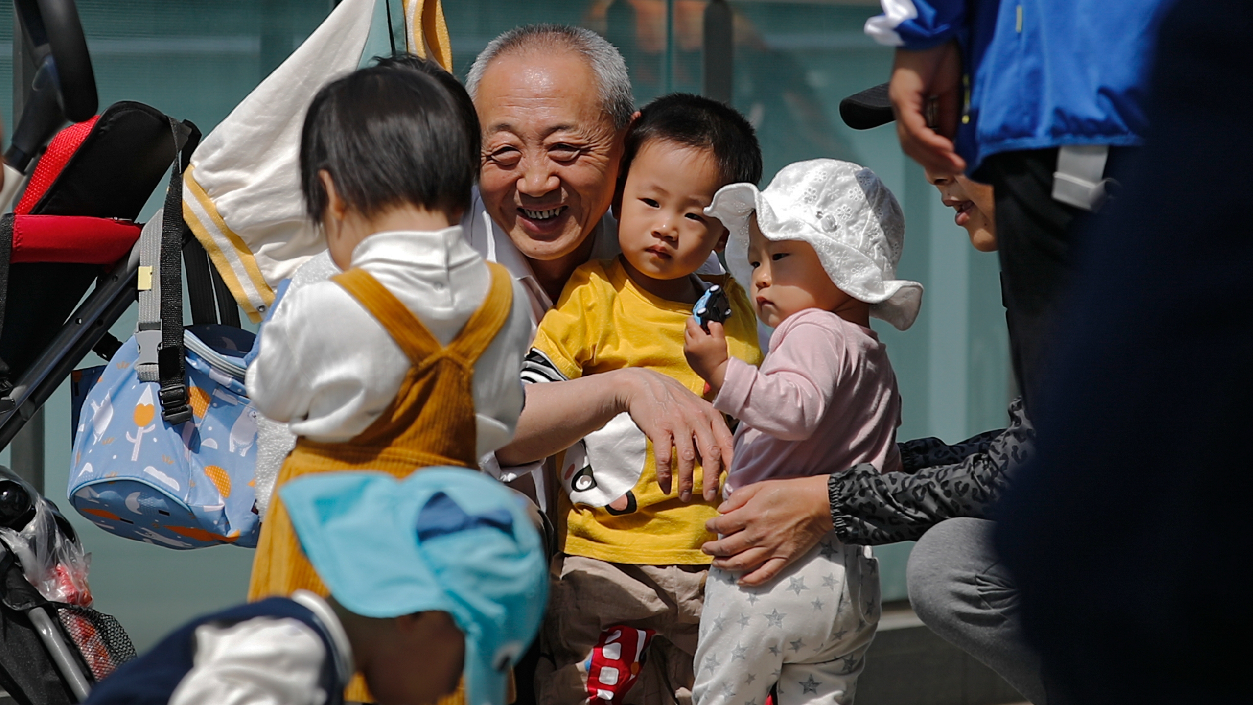 A man plays with children near a commercial office building in Beijing on May 10, 2021. China's ruling Communist Party will ease birth limits to allow all couples to have three children instead of two to cope with the rapid rise in the average age of its population, a state news agency said Monday, May 31. (AP Photo/Andy Wong)