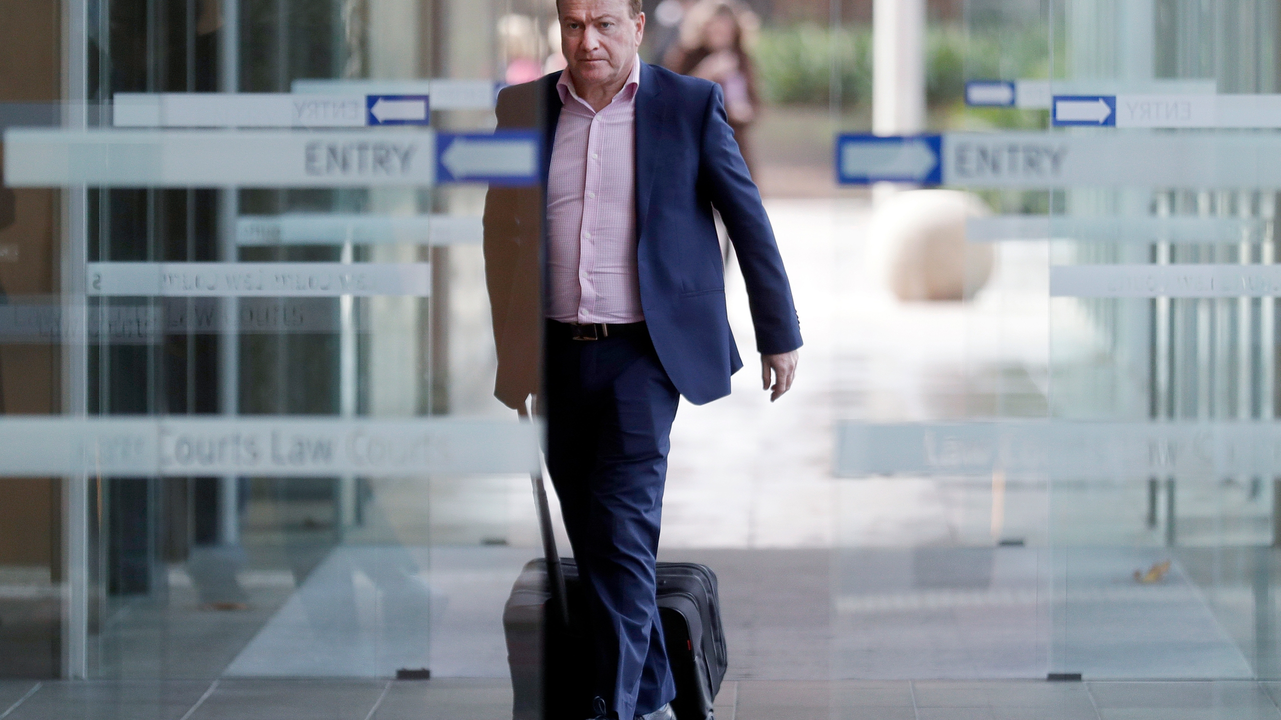 In this May 6, 2021, file photo, Andrew Cooper, founder and president of libertarian group LibertyWorks, arrives at Federal Court in Sydney. (AP Photo/Rick Rycroft, File)