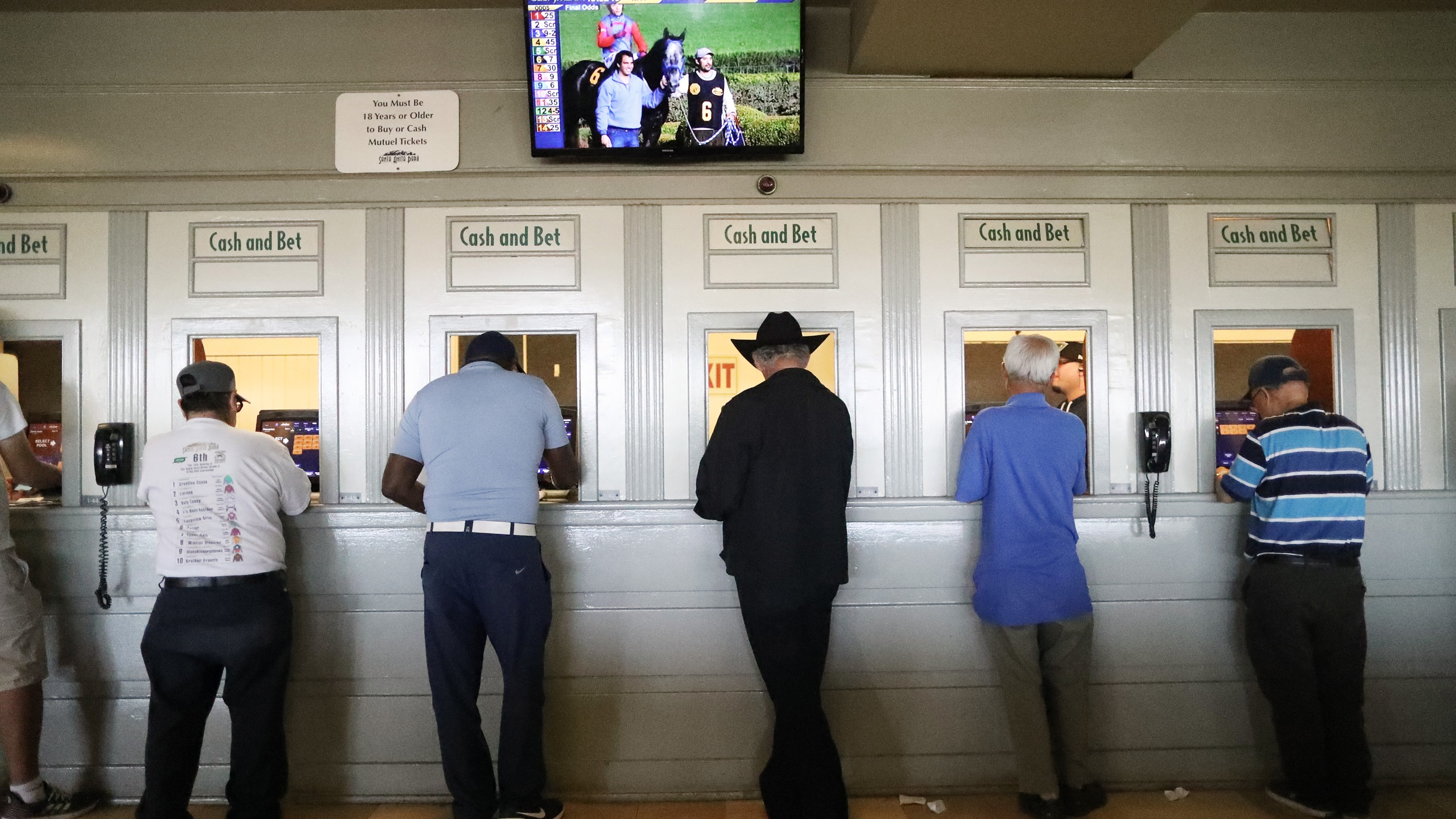Gamblers stand at betting windows on the final day of the winter/spring horse racing season at Santa Anita Park on June 23, 2019 in Arcadia, California. (Mario Tama/Getty Images)