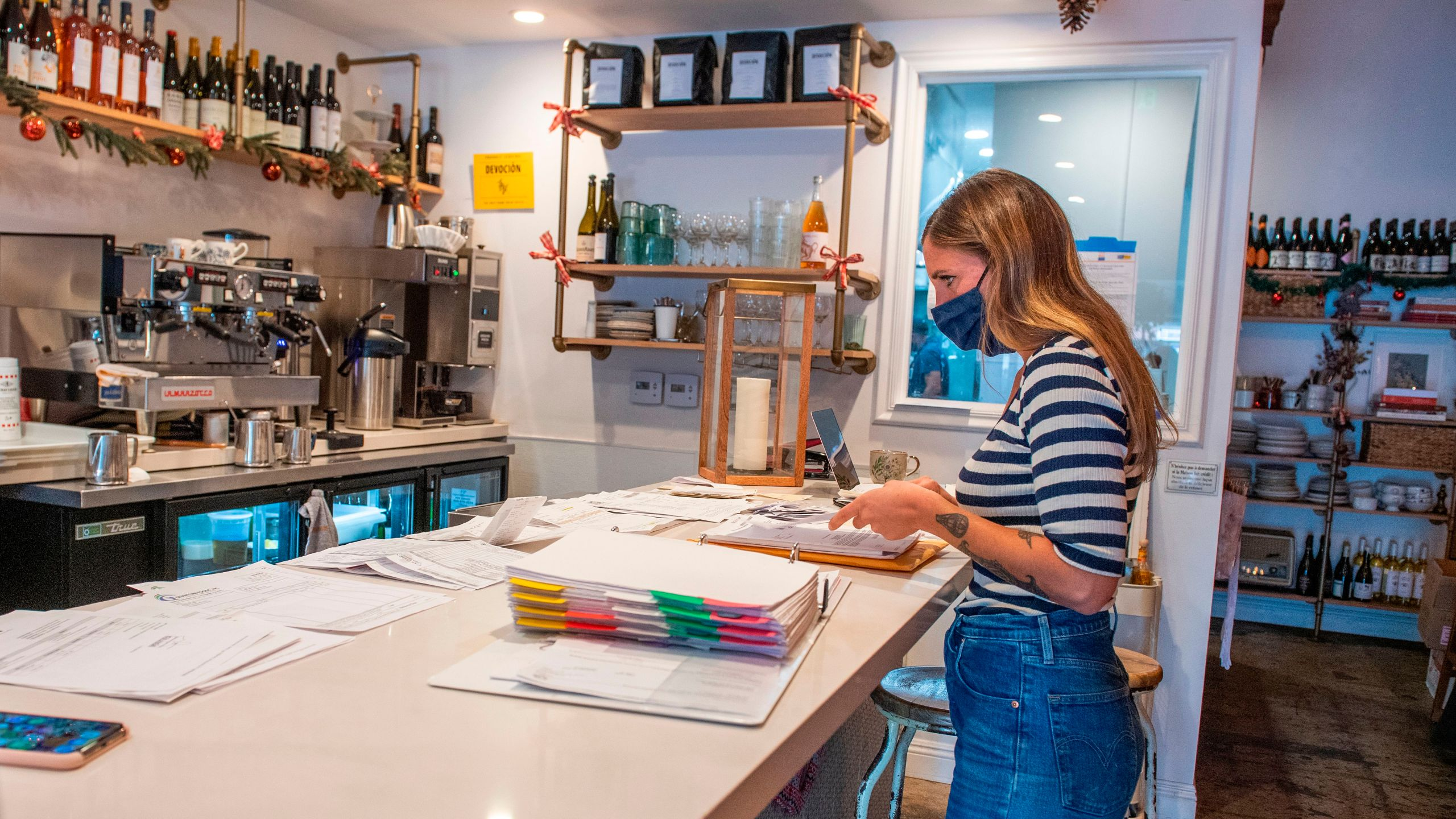 """Sarah Bessade, owner of """"La Loupiotte Kitchen"""", a restaurant in Los Angeles, works on her accounts in the restaurant's kitchen on Dec. 8, 2020. (VALERIE MACON/AFP via Getty Images)"""