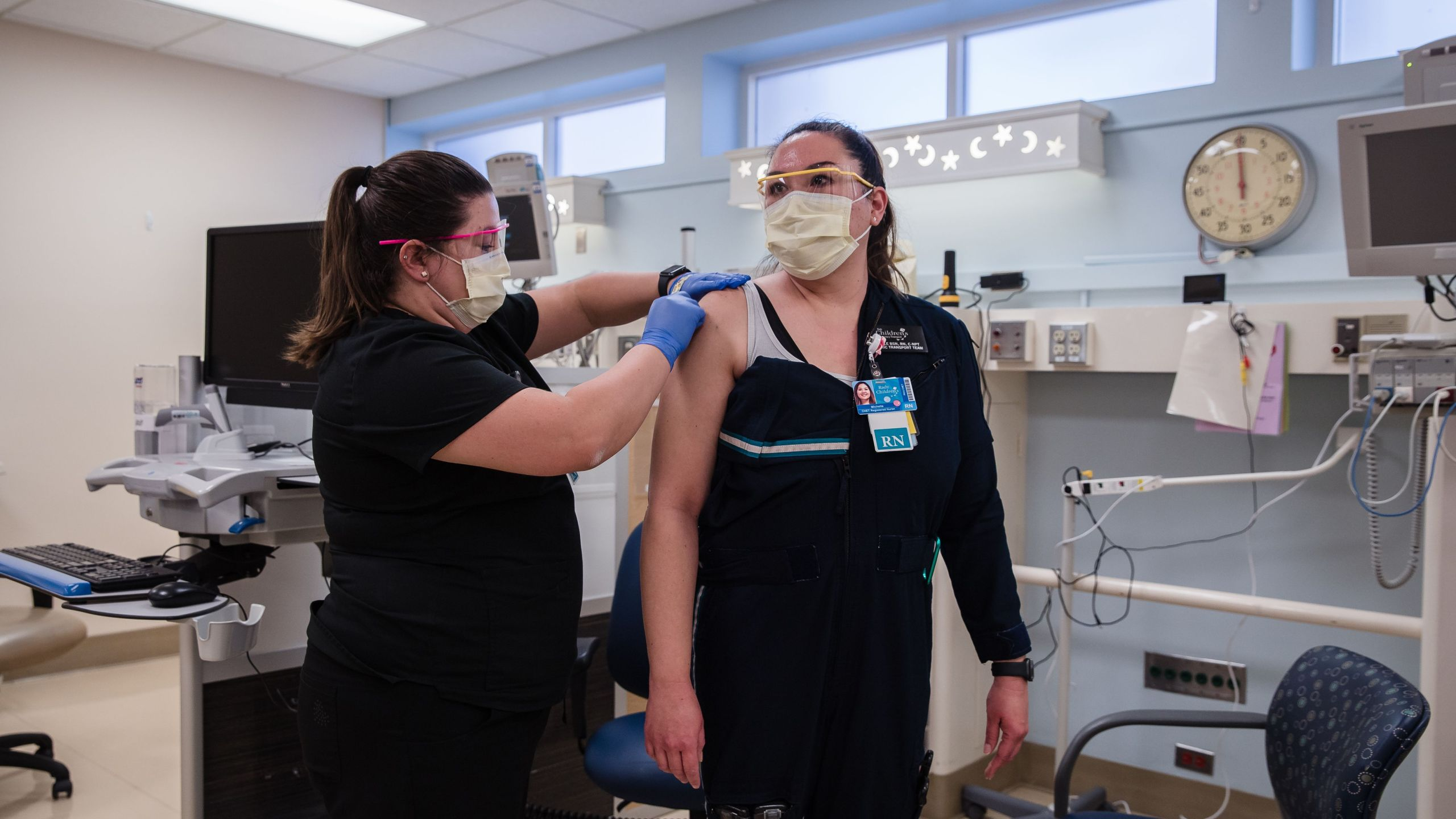 Rachel Marrs (L) gives the Pfizer-BioNTech Covid-19 Vaccine shot to Michelle Gaano a Registered Nurse at Rady Children's Hospital in San Diego, California on December 15, 2020. (ARIANA DREHSLER / AFP via Getty Images)