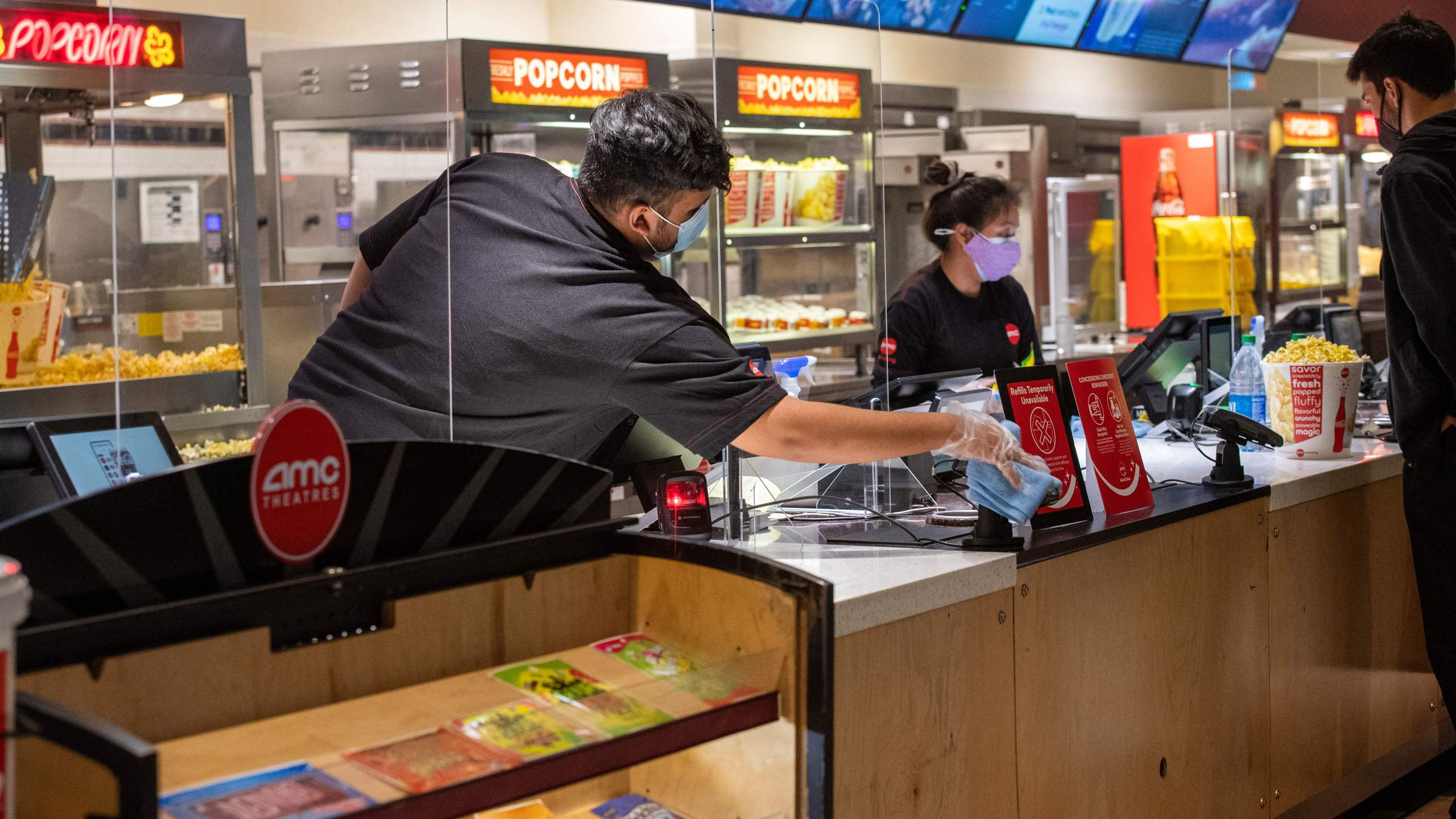 An AMC employe sanitize the counter after each customer at the AMC Burbank theatre concession stand on reopening day in Burbank, California, March 15, 2021. (Valerie Macon/AFP via Getty Images)