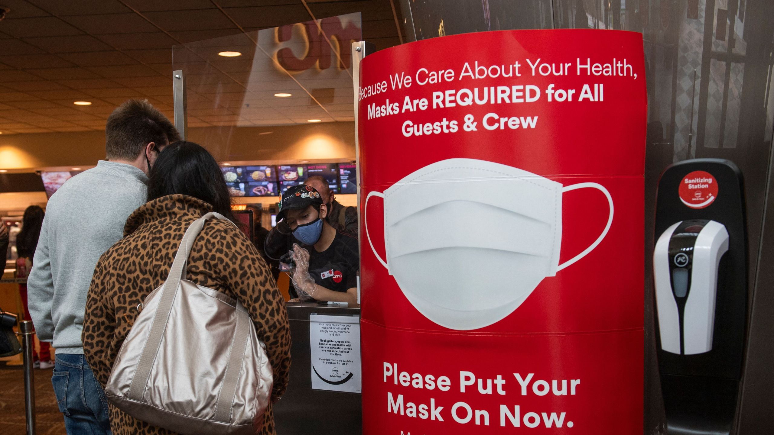 A sign asking people to wear a mask is displayed as moviegoers buy tickets at the AMC Burbank theatre on reopening day on March 15, 2021. (VALERIE MACON/AFP via Getty Images)