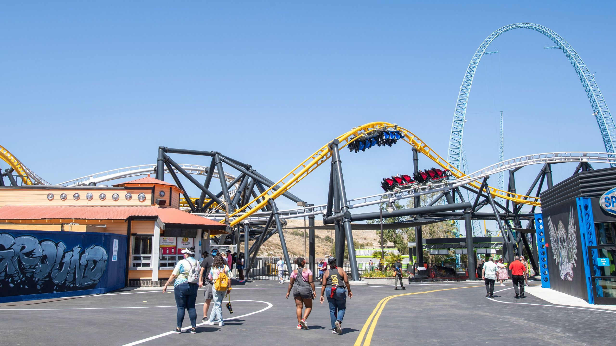 Visitors walk past the West Coast Racers roller coaster at Six Flags Magic Mountain on April 1, 2021. (VALERIE MACON/AFP via Getty Images)