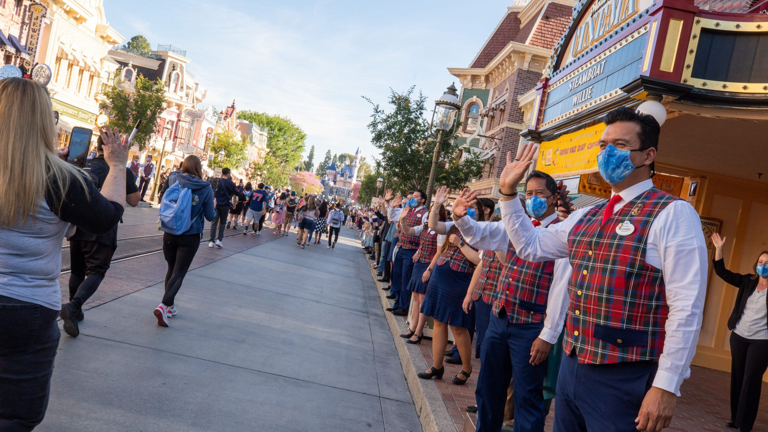 In this handout photo provided by Disneyland Resort, guests are waved to by workers as they take in the sights and sounds of Main Street U.S.A. at the Disneyland Resort on April 30, 2021 in Anaheim, Calif. Guests are being welcomed back as Disneyland Park, Disney California Adventure Park and Disney's Grand Californian Hotel & Spa are reopening. (Christian Thompson/Disneyland Resort via Getty Images)