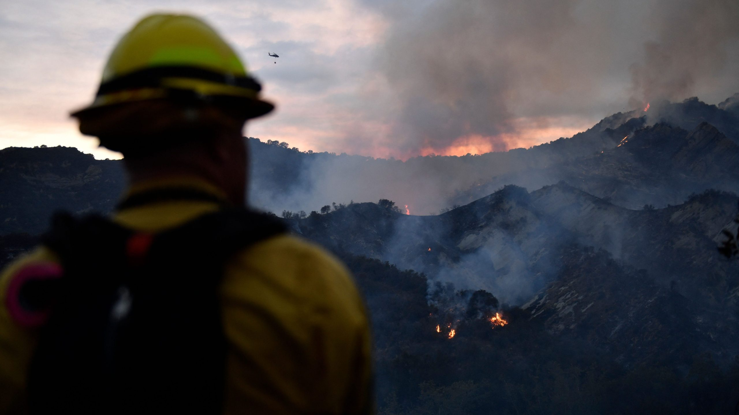 A firefighter watches the flames from the Palisades Fire as helicopters make water drops in the distance in Topanga State Park, northwest of Los Angeles, on May 15, 2021. (PATRICK T. FALLON / AFP / Getty Images)