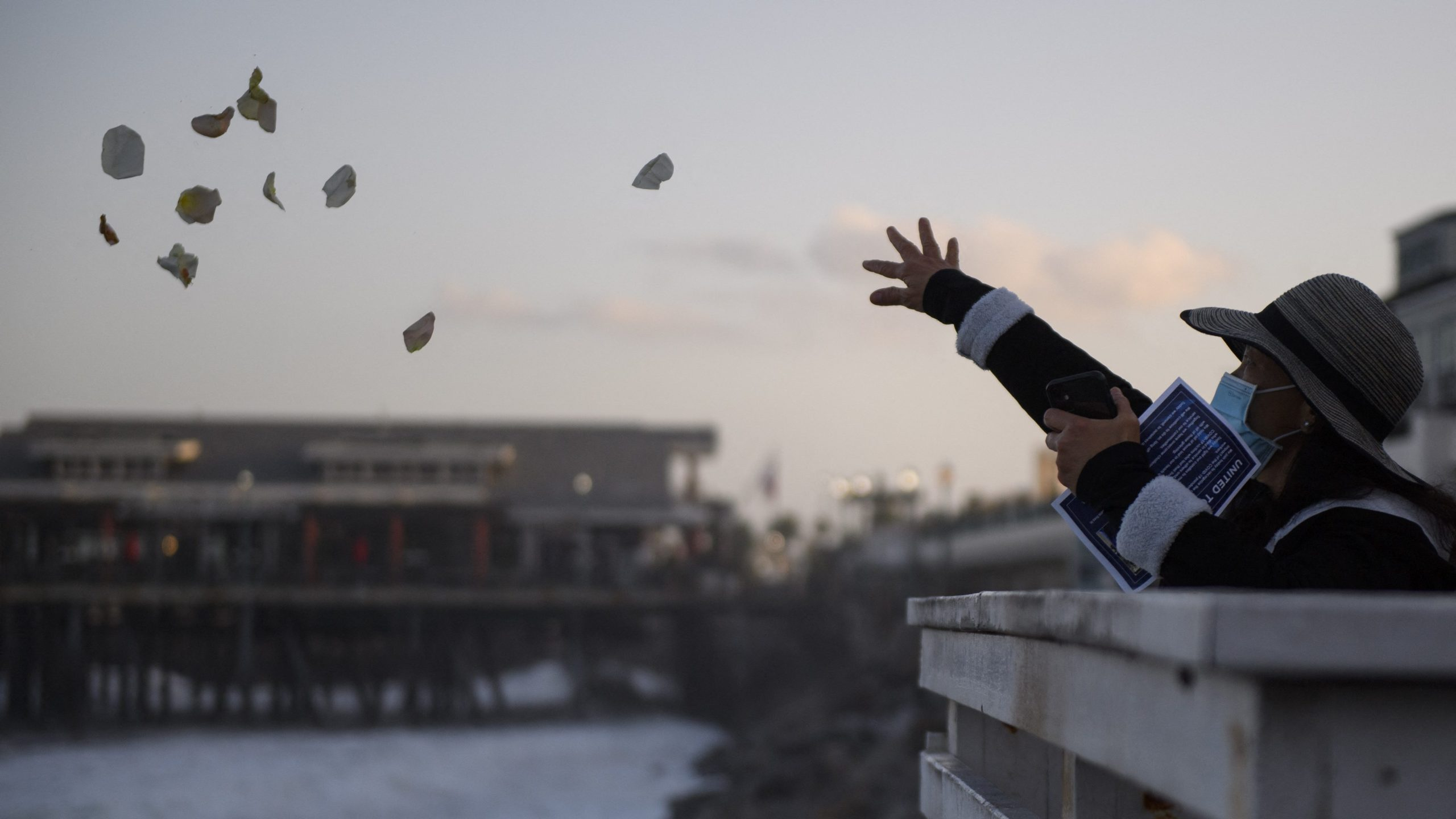 People throw rose petals into the Pacific Ocean during a sunrise vigil organized by United Nurses Associations of California/Union of Health Care Professionals (UNAC/UHCP) at the Redondo Beach Pier on May 22, 2021, to remember health care workers and patients who died from the COVID-19 pandemic. (Patrick T. Fallon / AFP / Getty Images)