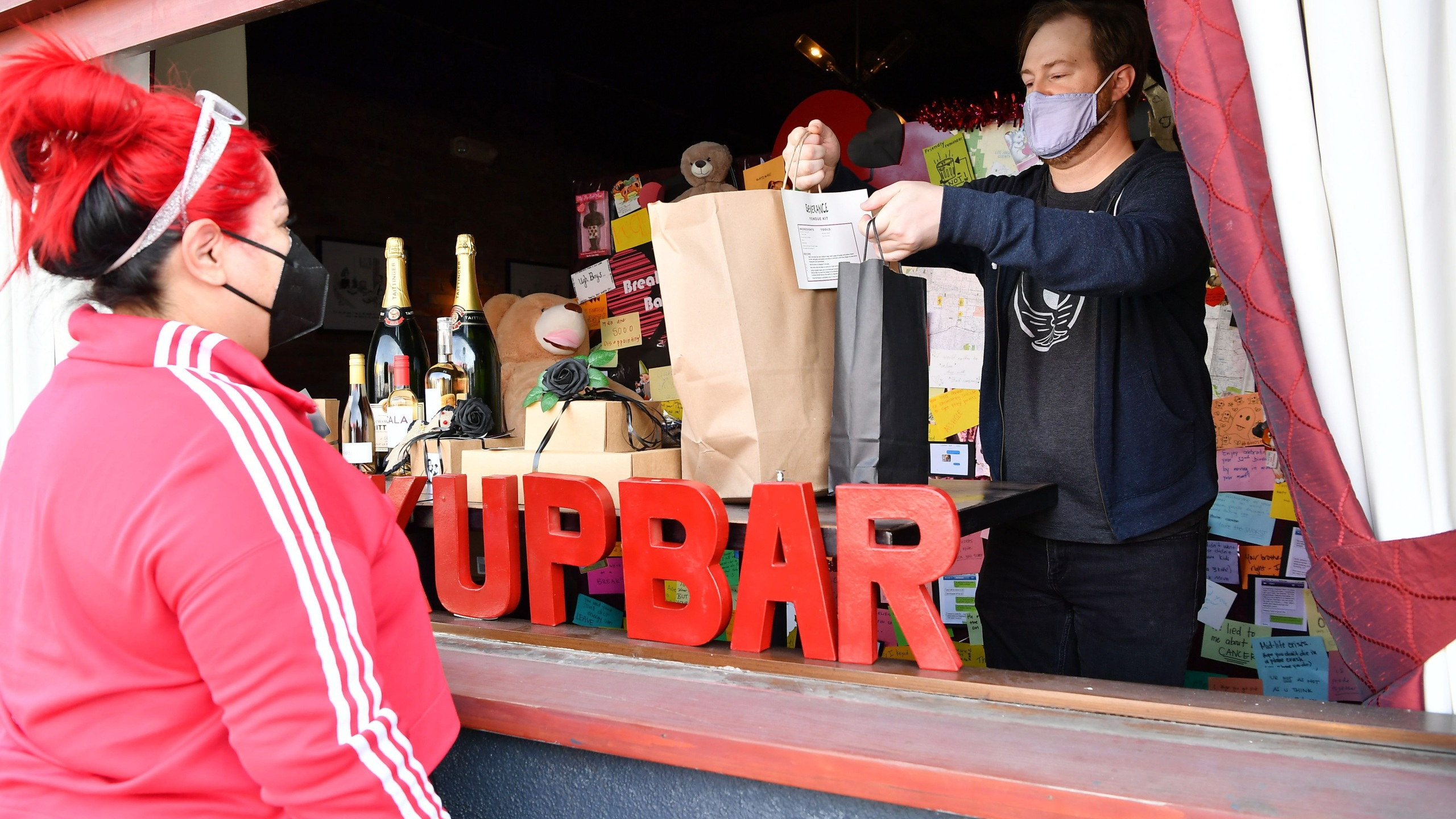 Owner Evan Charest helps a customer with her order at the Break Up Bar, which celebrated its 3-year anniversary on Valentine's Day on Feb. 13, 2021 in Los Angeles. (Amy Sussman/Getty Images)