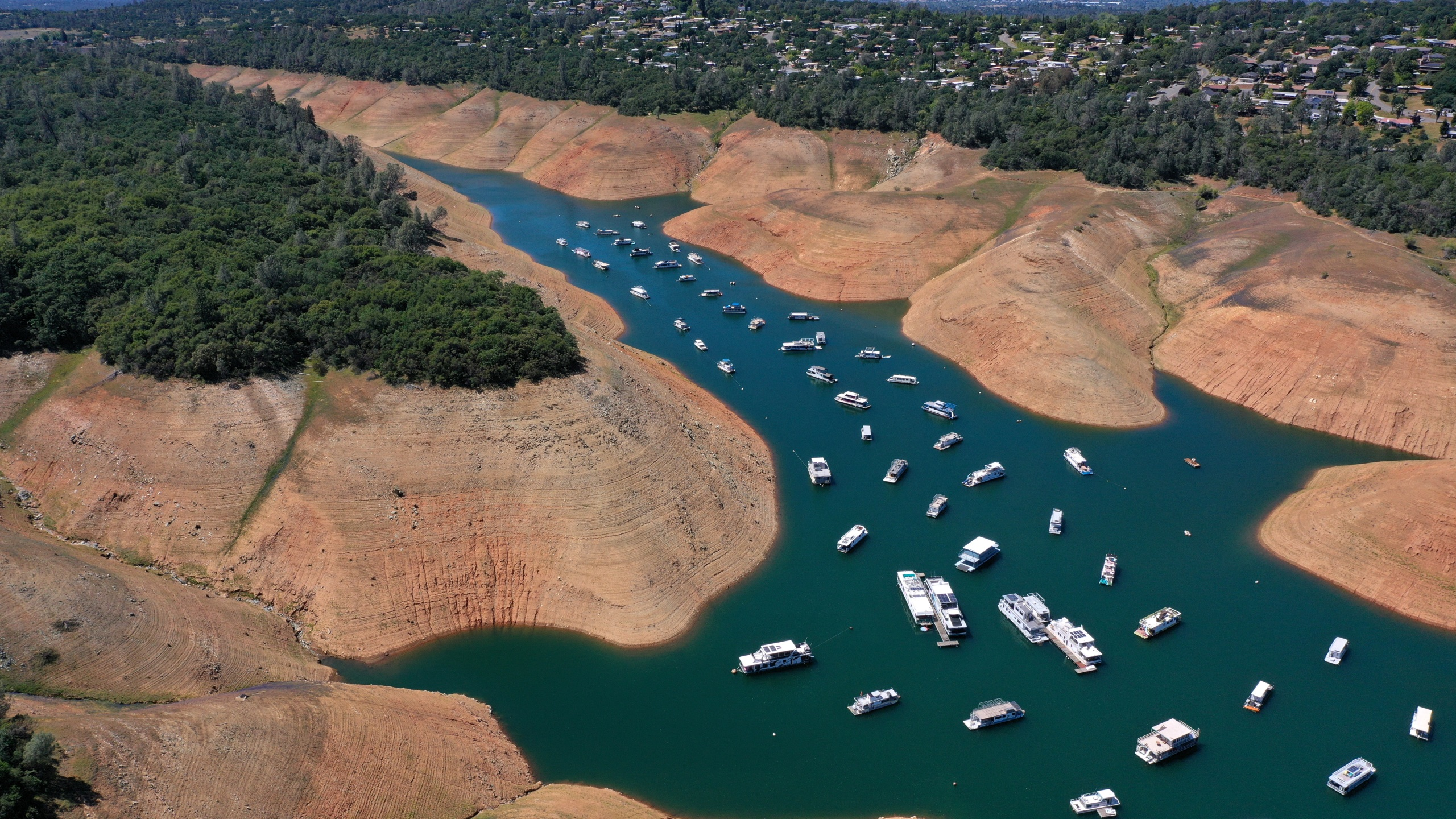 In an aerial view, houseboats are dwarfed by the steep banks of Lake Oroville on April 27, 2021 in Oroville, California.(Justin Sullivan/Getty Images)