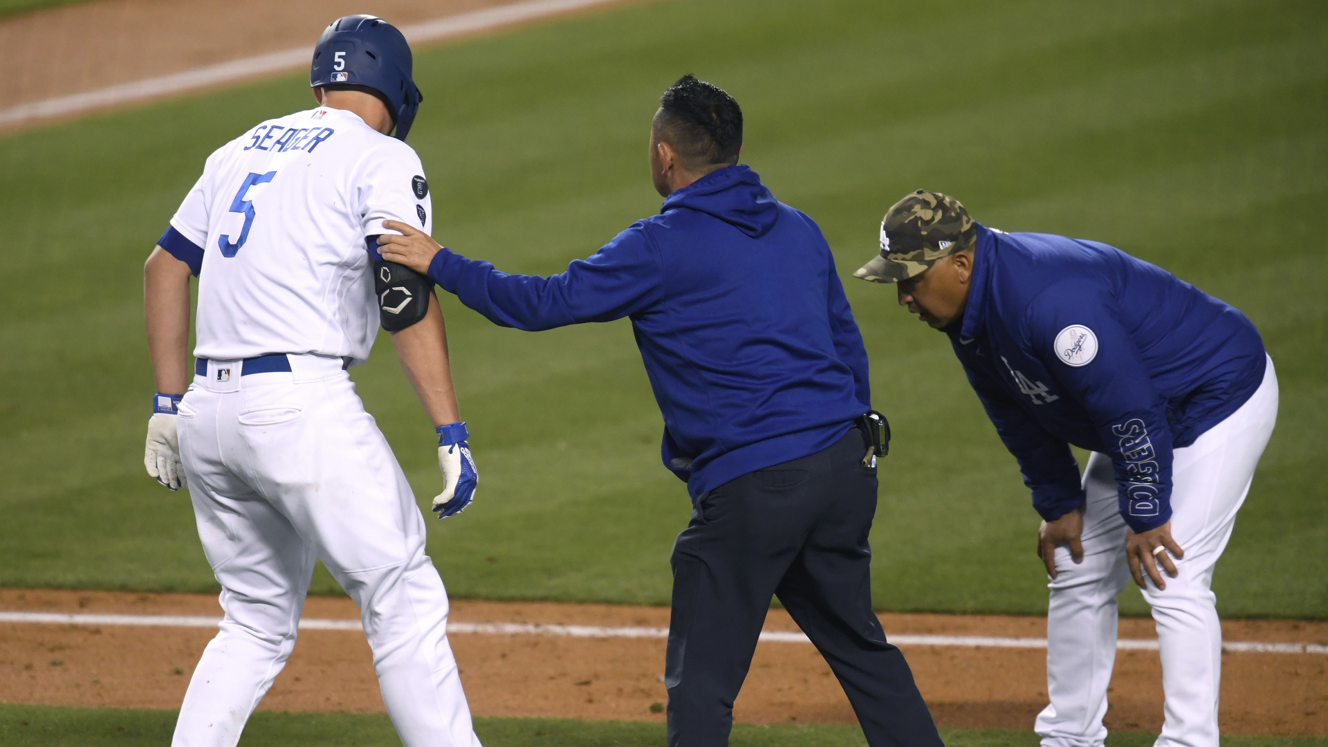 Corey Seager #5 of the Los Angeles Dodgers is helped by Dodgers medical staff after he was hit by a pitch, as Dave Roberts #30 looks on, during the fifth inning at Dodger Stadium on May 15, 2021 in Los Angeles. (Harry How/Getty Images)