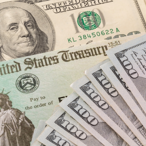 A U.S. Treasury check and $100 bills are seen in a file photo. (iStock/Getty Images Plus)