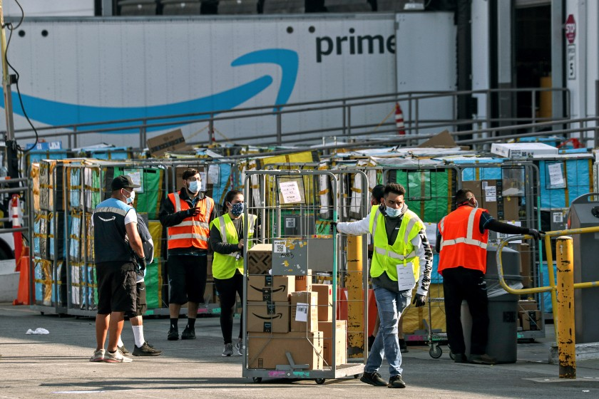 Delivery vans leave an Amazon warehouse facility in Hawthorne in this undated photo. The company is being fined by Cal OSHA for COVID-19 workplace safety failings in a second round of California citations in May 2021. (Irfan Khan / Los Angeles Times)
