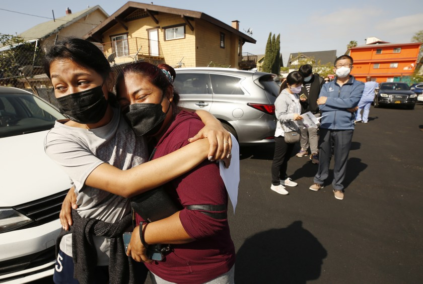 Jeymy Mendoza, 16, hugs her mother, Maria Jimenez, 34, as they wait in line in April to receive the Pfizer COVID-19 vaccination at a walk-up mobile clinic in Los Angeles. (Al Seib / Los Angeles Times)