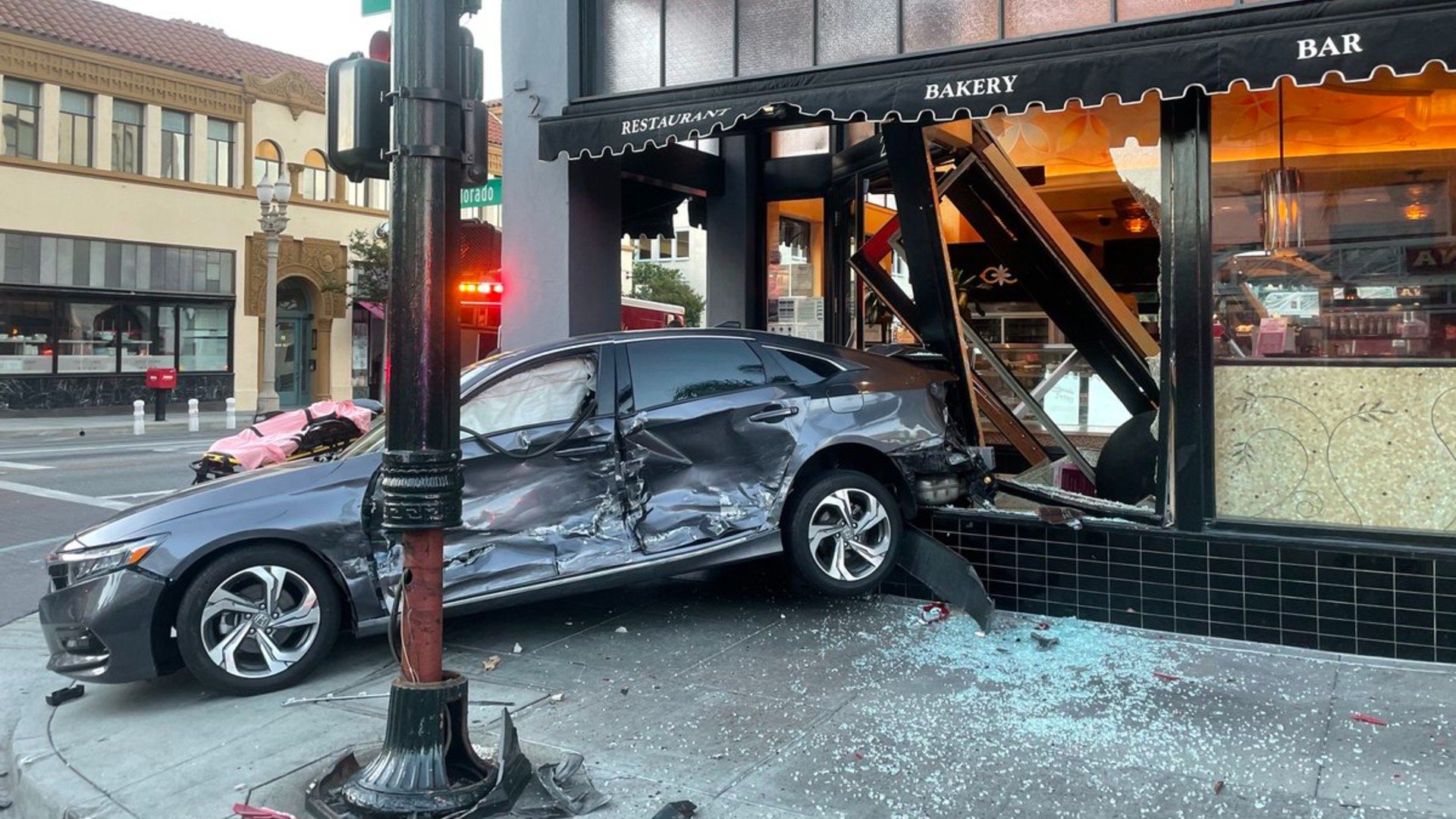A car careened into the storefront of the Cheesecake Factory in Old Town Pasadena on Tuesday morning after a collision in an intersection.(Pasadena Fire Department )
