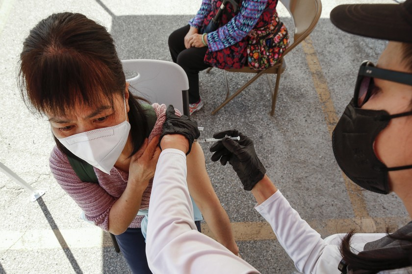 A woman receives a COVID-19 vaccination at a mobile clinic in Chinatown.(Al Seib / Los Angeles Times)