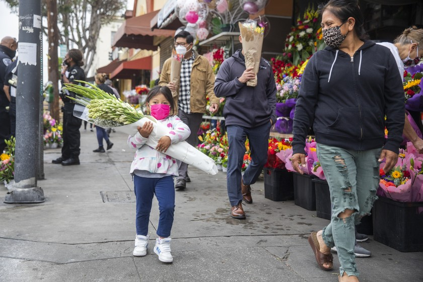 Andrea Fabian, 4, of Inglewood carries flowers while walking with her mother, Amelia Cruz, along San Pedro Street. There are several factors driving the flower shortage, many of which can be tied to the COVID-19 pandemic, industry experts said. (Mel Melcon / Los Angeles Times)
