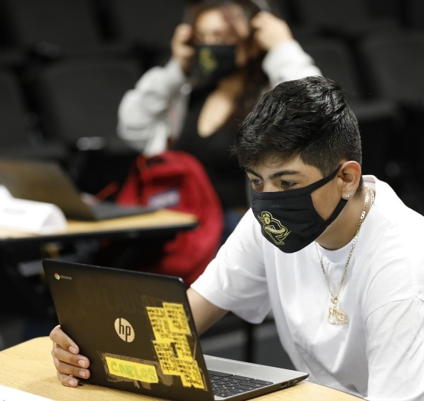 """Ninth-grader Carlos """"Jairo"""" Zamora, 16, logs in via Zoom to classes in another part of the building as he sits in the Panorama High School classroom of drama teacher Patricia Francisco.(Al Seib / Los Angeles Times)"""