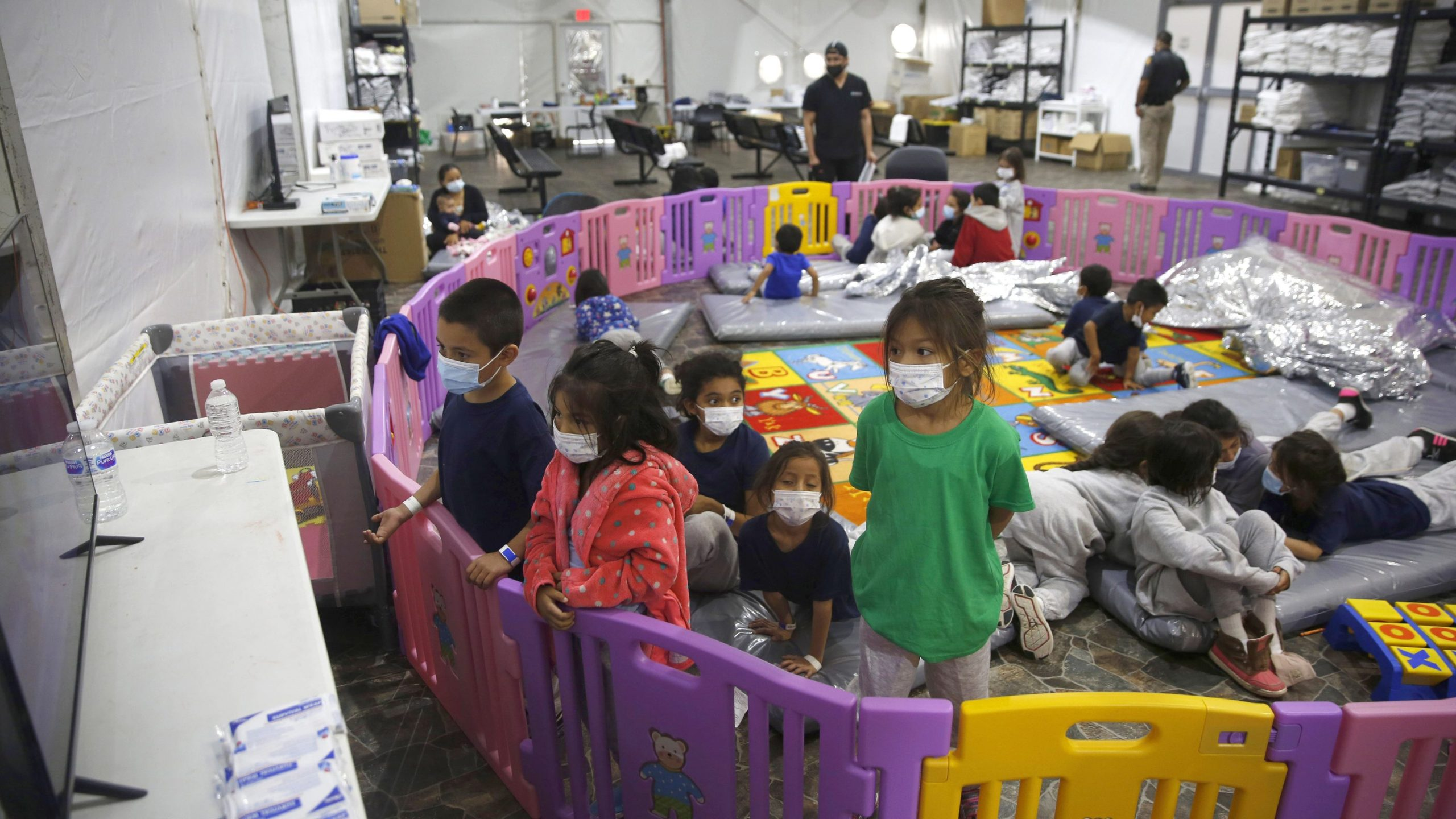 Young unaccompanied migrants, from ages 3 to 9, watch television inside a playpen at the U.S. Customs and Border Protection facility in Donna, Texas, the main detention center for unaccompanied children in the Rio Grande Valley. (Dario Lopez-Mills / Associated Press)