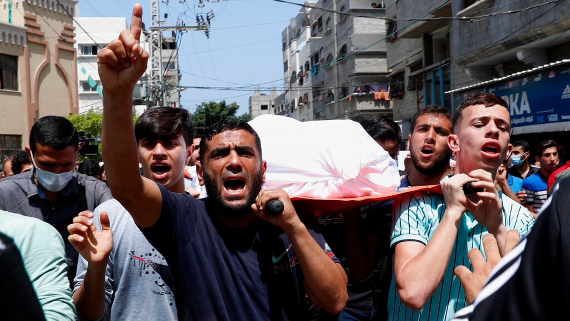 Mourners chant Islamic slogans while they carry the body of Amira Soboh, and her 19-year-old disabled son Abdelrahman, who were killed in Israeli airstrikes at their apartment building, during their funeral at the Shati refugee camp, in Gaza City, Tuesday, May 11, 2021. (AP Photo/Adel Hana)
