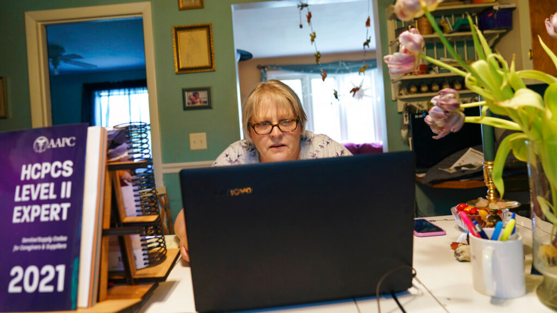 Ellen Booth, 57, studies at her kitchen table to become a certified medical coder, in Coventry, R.I., Monday, May 17, 2021. (AP Photo/David Goldman)
