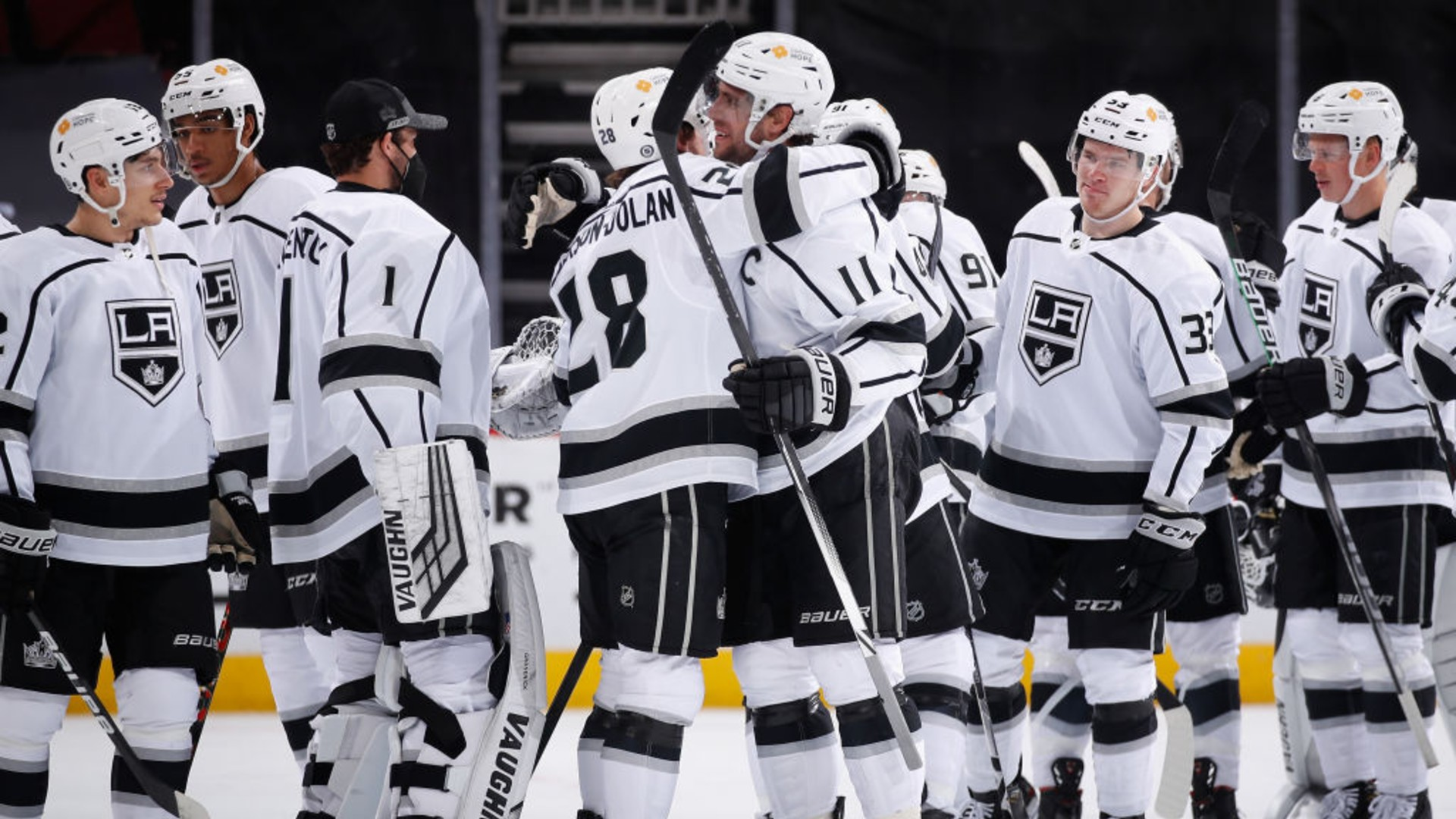 Anze Kopitar #11 of the Los Angeles Kings hugs Jaret Anderson-Dolan #28 after defeating the Arizona Coyotes and recording his 1,000th career point in the NHL game against the Arizona Coyotes at Gila River Arena on May 05, 2021 in Glendale, Arizona. (Christian Petersen/Getty Images)