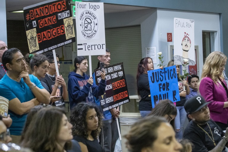 East Los Angeles residents, activists and relatives of people shot by deputies hold signs while attending the Sheriff Civilian Oversight Commission town hall in 2019. (Allen J. Schaben / Los Angeles Times)