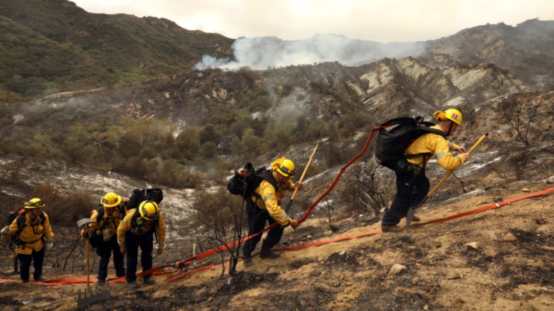Firefighters work between Pacific Palisades and Topanga Canyon as air drops continued Sunday.(Carolyn Cole / Los Angeles Times)