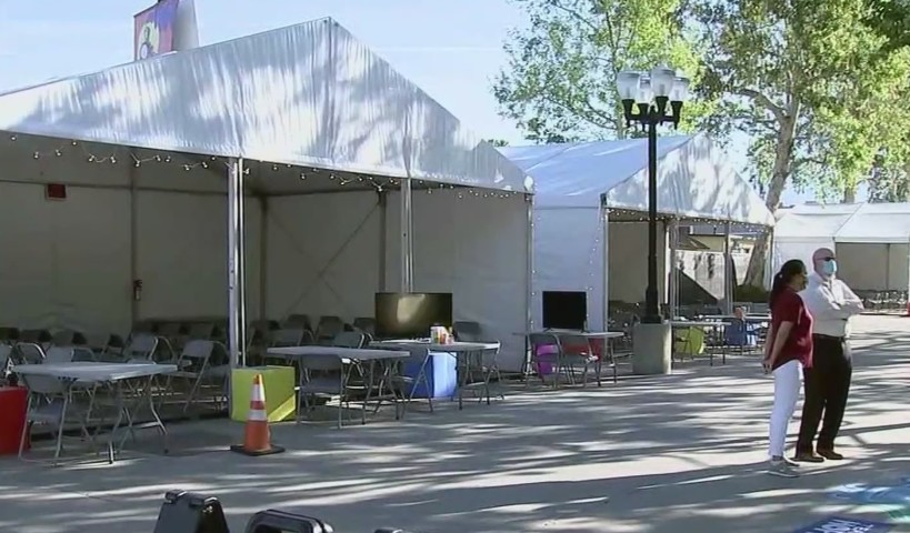 People at the Pomona Fairplex prepare for the arrival of 250 migrant children May 1, 2021, as the facility is expected to temporarily house the minors. (KTLA)