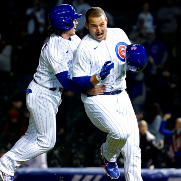 Chicago Cubs' Tony Wolters, left, congratulates Anthony Rizzo, who drove in the winning run in the 11th inning of a baseball game against the Los Angeles Dodgers in Chicago, Wednesday, May 5, 2021. The Cubs won 6-5. (AP Photo/Nam Y. Huh)