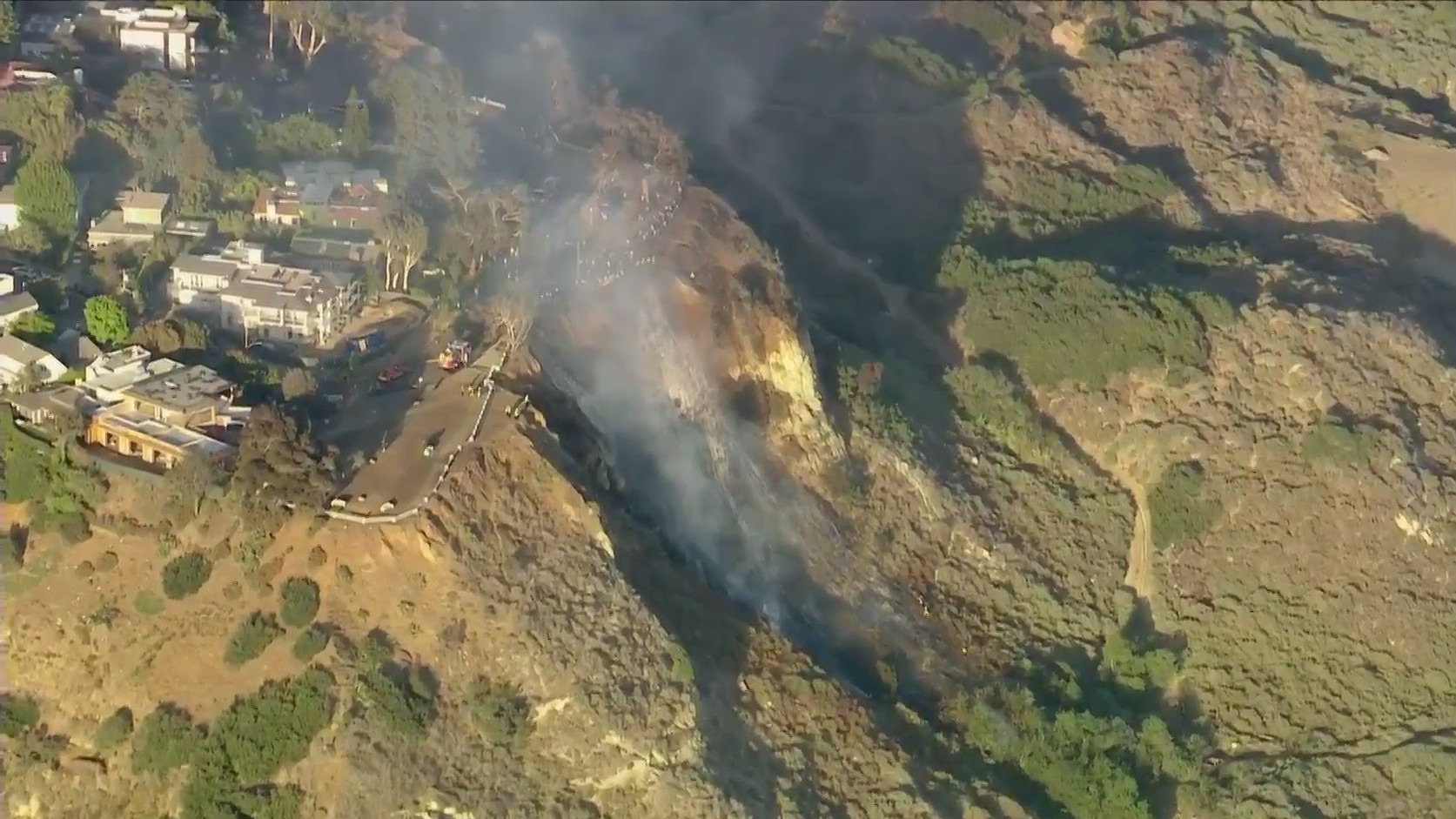 Firefighters work to fully extinguish a brush fire that broke out along Highway 1 in Pacific Palisades on May 24, 2021. (KTLA)
