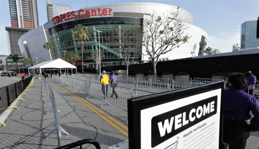 A slow trickle of fans head toward the Staples Center entrance for the Lakers-Celtics game on April 15, 2021. The Lakers are extending their lease with the arena. (Myung Chun / Los Angeles Times)