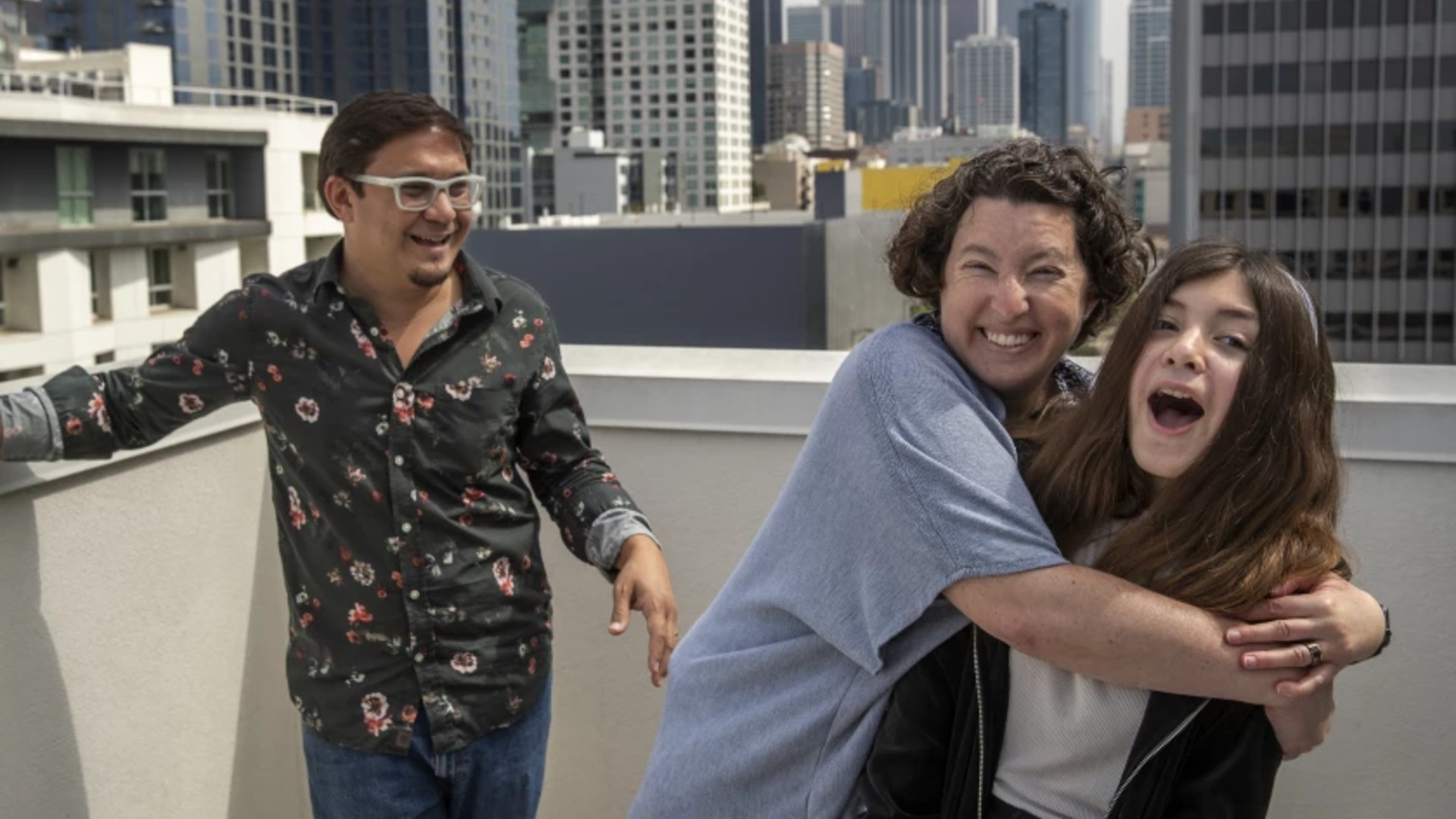 Alex Brideau, his wife, Ginny, and daughter, Iolani, 12, on the rooftop of their apartment building in downtown Los Angeles. The Brideaus have secured an appointment for their daughter to be vaccinated Monday.(Mel Melcon / Los Angeles Times)