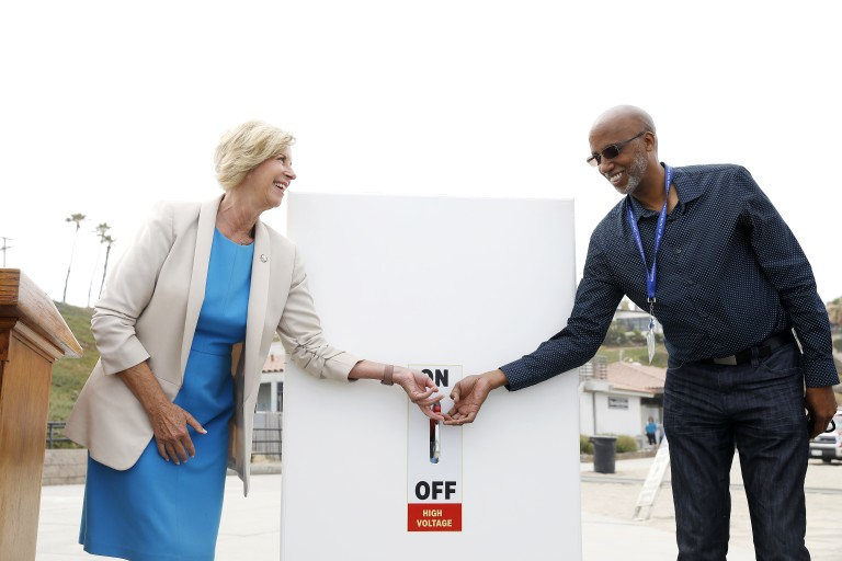 L.A. County Supervisor Janice Hahn and Randy Dean, creator of the Beach Emergency Evacuation Lights System, flip a switch to begin a demonstration of the system at Torrance Beach on July 18, 2021.(Christina House / Los Angeles Times)