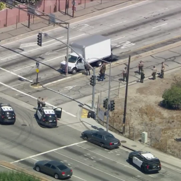 Officials block off an area where a driver was shot by L.A. County sheriff's deputies in Norwalk on June 23, 2021. (KTLA)
