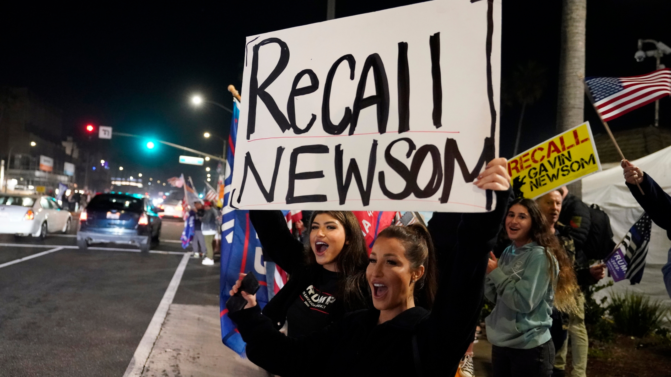 In this Saturday, Nov. 21, 2020, file photo, demonstrators shout slogans while carrying a sign calling for a recall on Gov. Gavin Newsom during a protest against a stay-at-home order amid the COVID-19 pandemic in Huntington Beach. (AP Photo/Marcio Jose Sanchez, File)