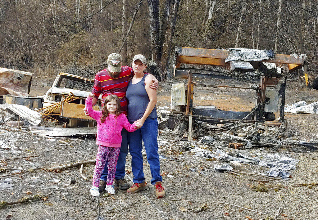 In this photo provided by Tye and Melynda Small, they are seen standing with their 5-year-old daughter, Madalyn, in front of the ruins of their home in Otis, Oregon after the Echo Mountain Fire in September, 2020. (Tye and Melynda Small via AP)