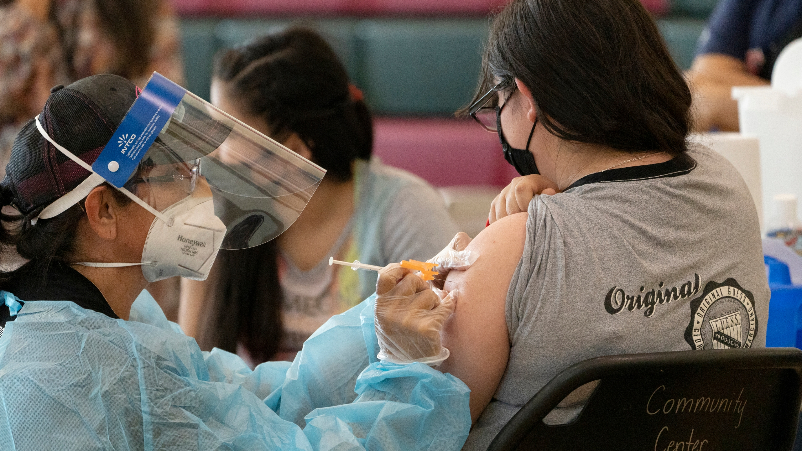 Sisters Guadalupe Flores, 15, right, and Estela Flores, 13, left, from East Los Angeles, get vaccinated with the Pfizer's COVID-19 vaccine by licensed vocational nurse Rita Orozco, far left, at the Esteban E. Torres High School in Los Angeles, Thursday, May 27, 2021. (AP Photo/Damian Dovarganes)