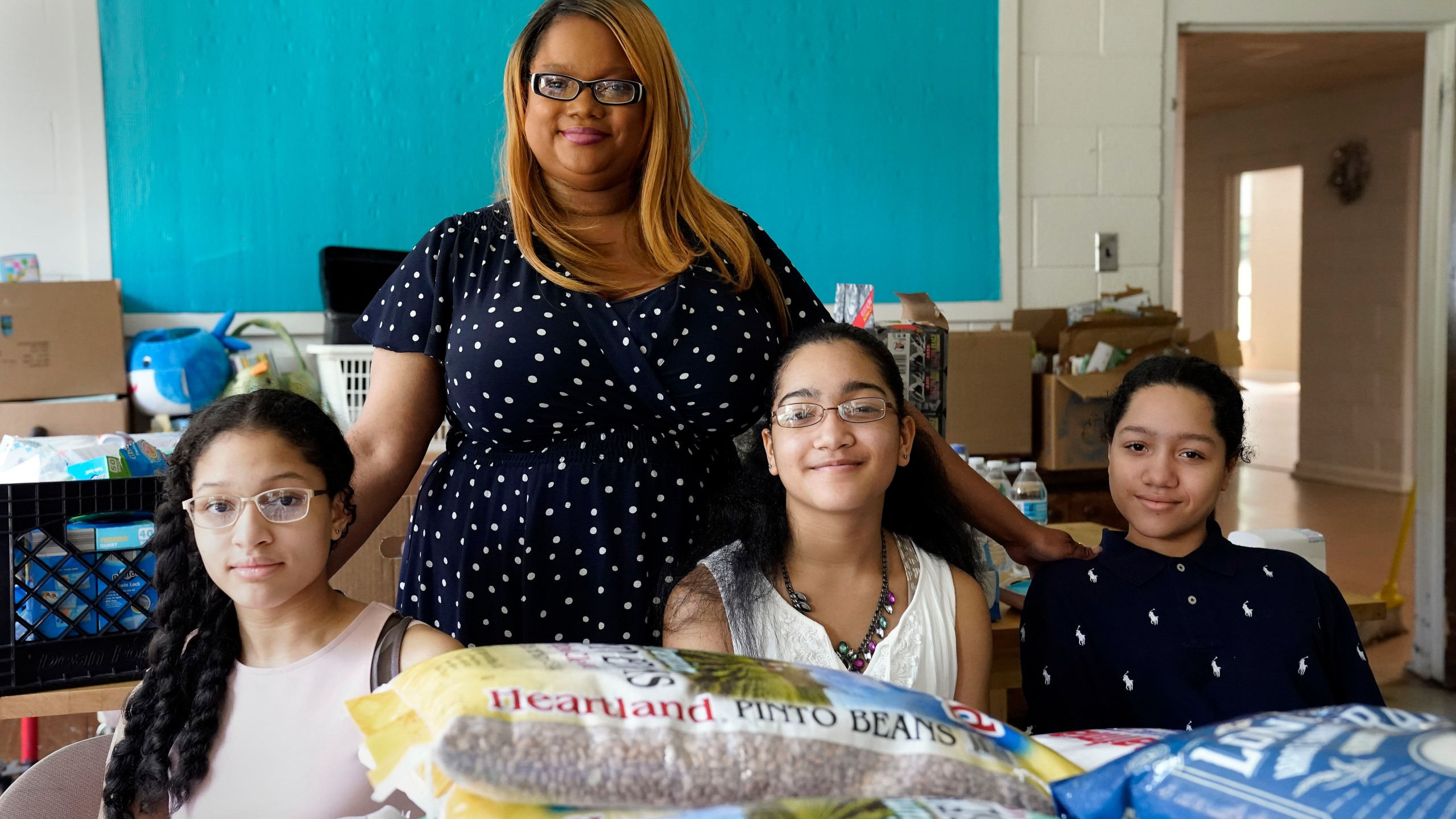 Aja Purnell-Mitchell stands next to her three children, Kyla, 13, left; Kyra, 15, and Cartier, 14, at a local food hub in Durham, N.C., on Friday, May 28, 2021, where they often help their mother. (AP Photo/Gerry Broome)